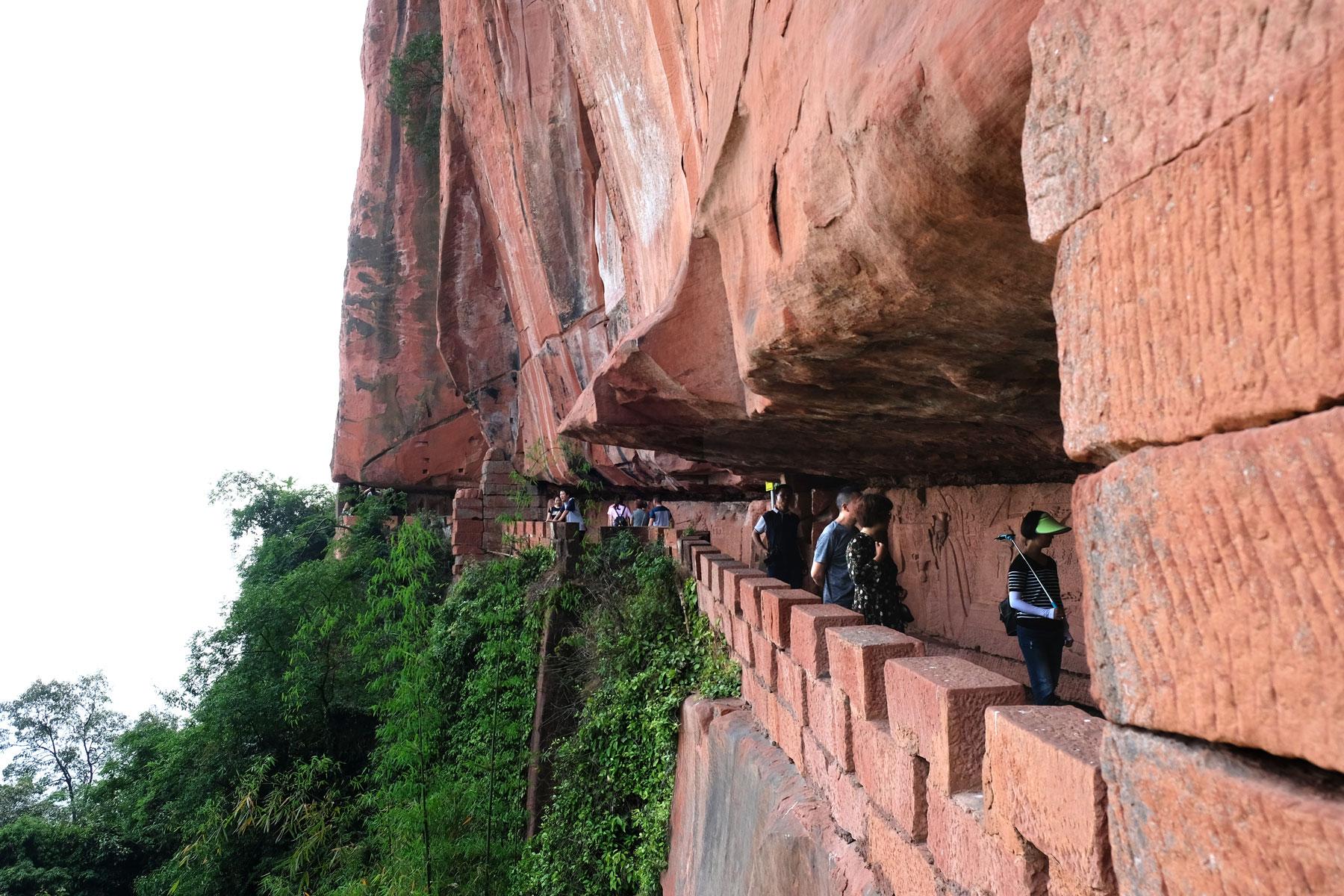Chinesische Touristen gehen auf einem Weg, der in roten Fels gehauen wurde.