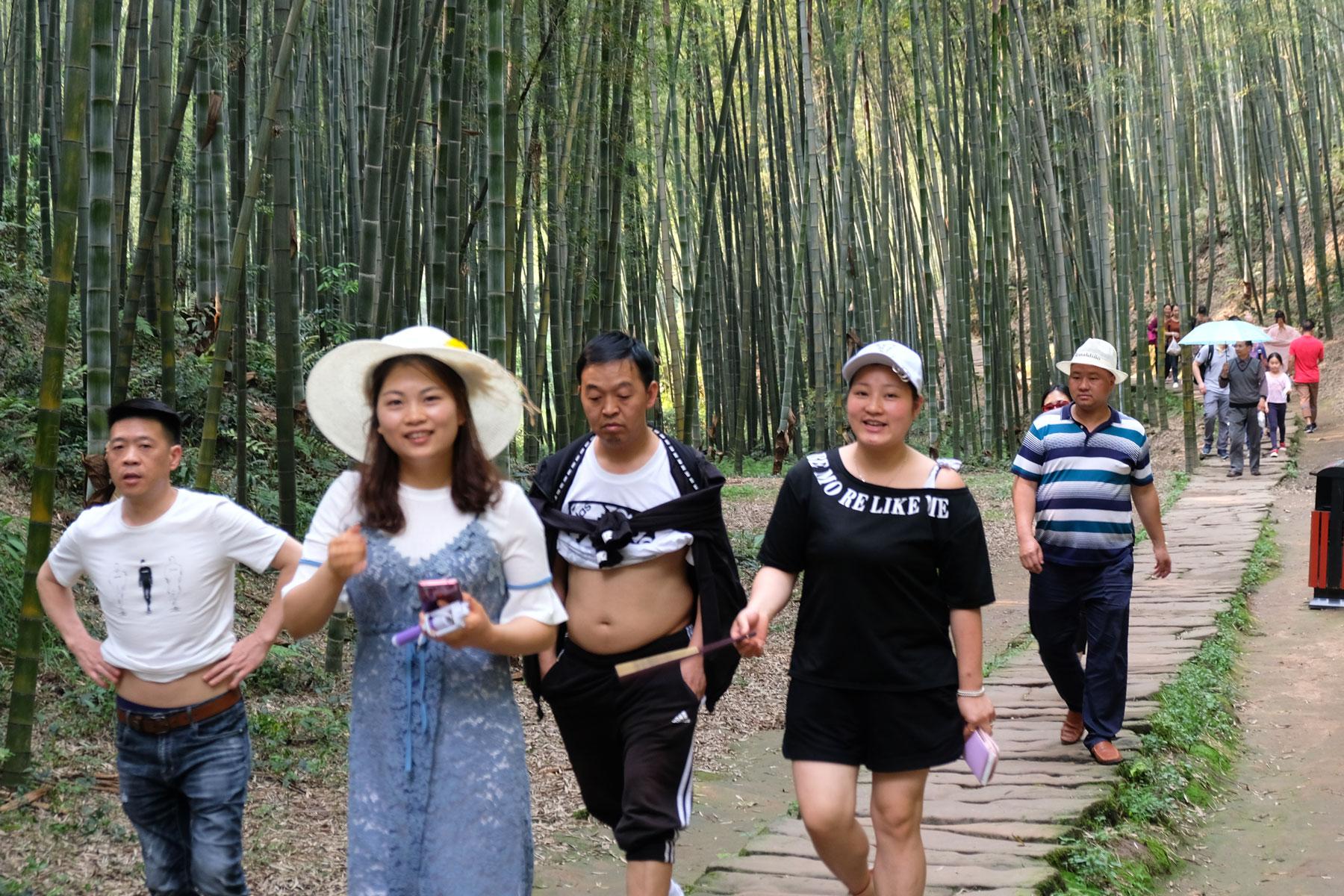 Chinesische Touristen gehen im Bambusmeer spazieren. Ein Chinese entblößt seinen Bauch.