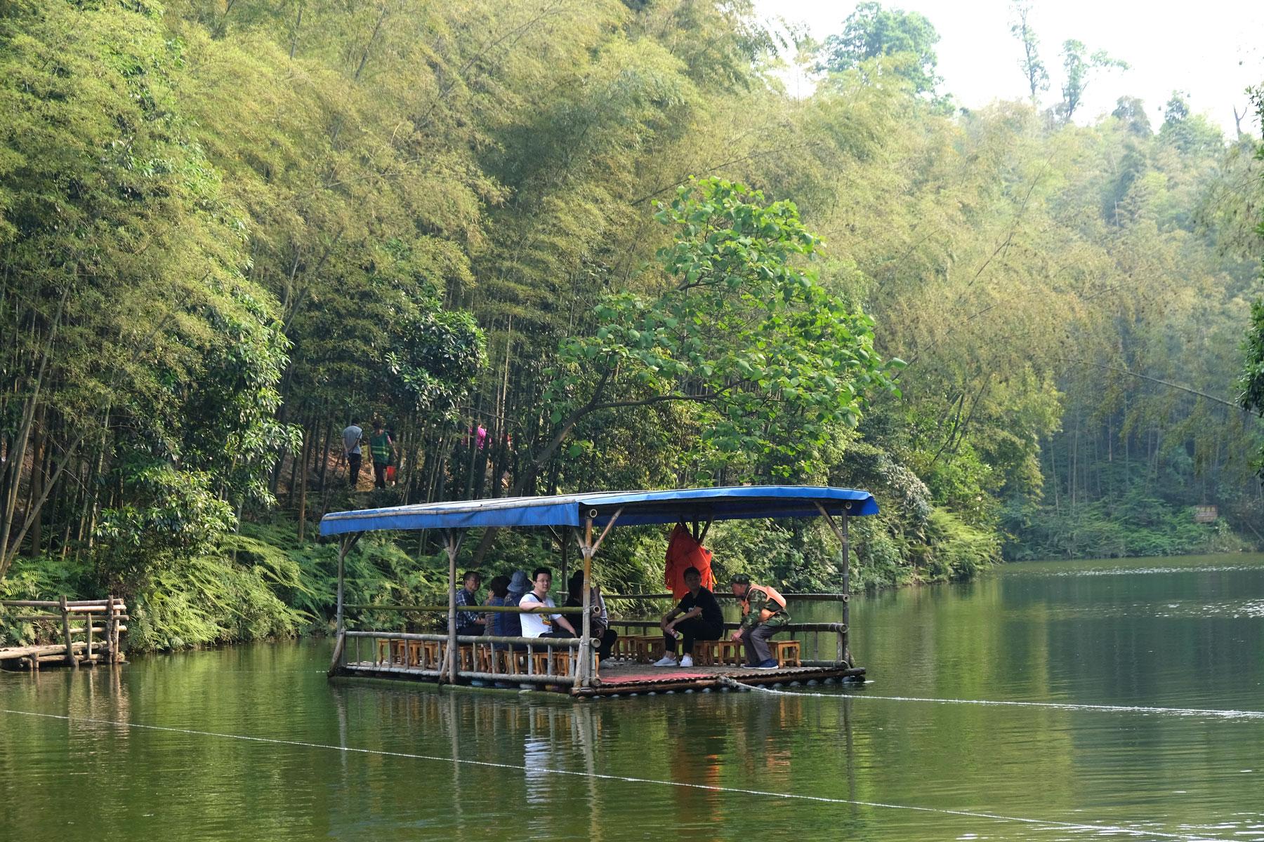 Ein Floß fährt auf einem See im Shunan Zhuhai Nationalpark.