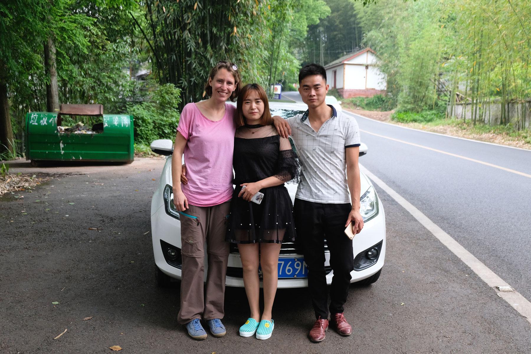 Leo steht mit einem chinesischen Pärchen vor einem Auto.