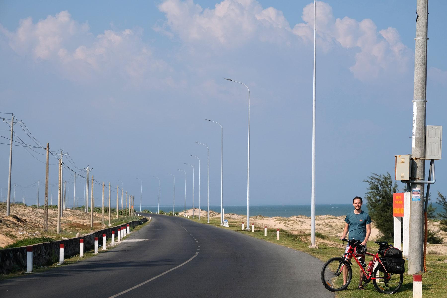 Sebastian steht mit einem Fahrrad an einer Straße in Vietnam.