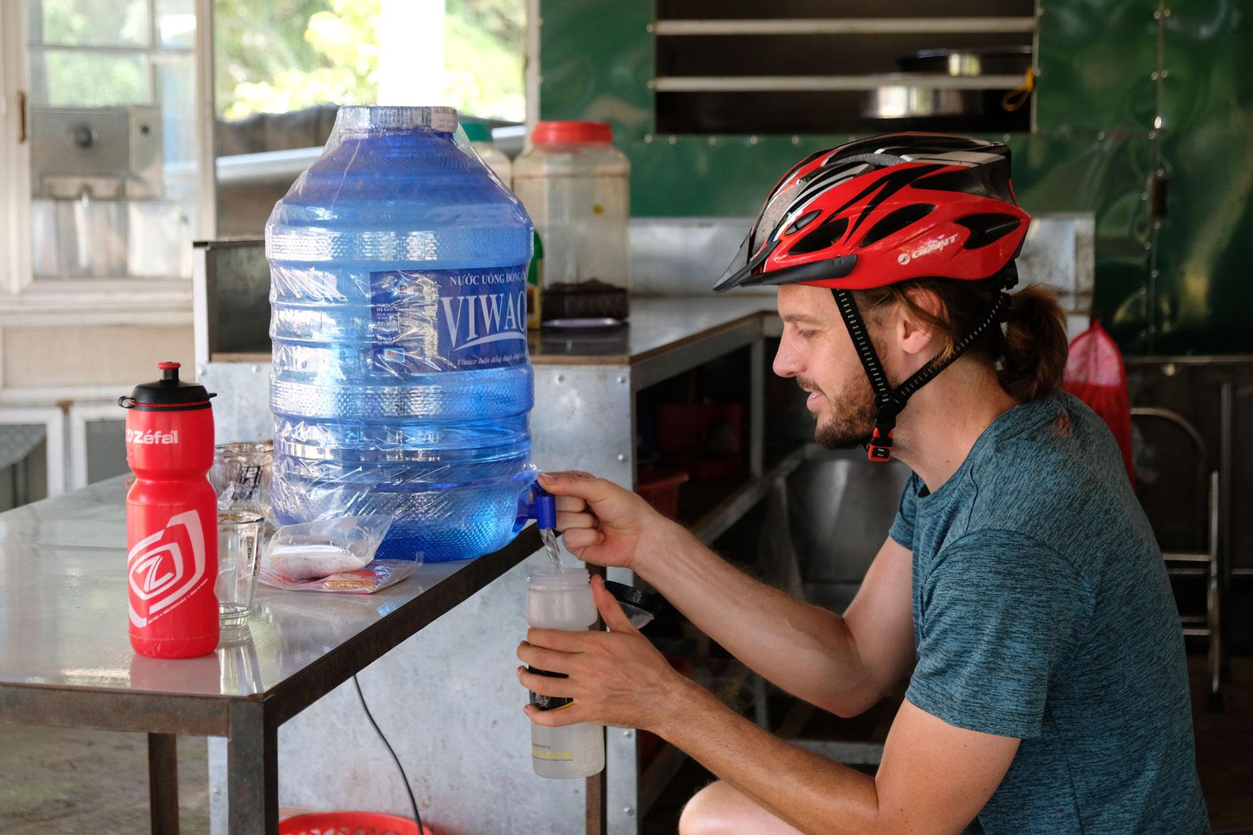 Sebastian trägt einen Fahrradhelm auf dem Kopf und zapft Trinkwasser aus einem Kanister.