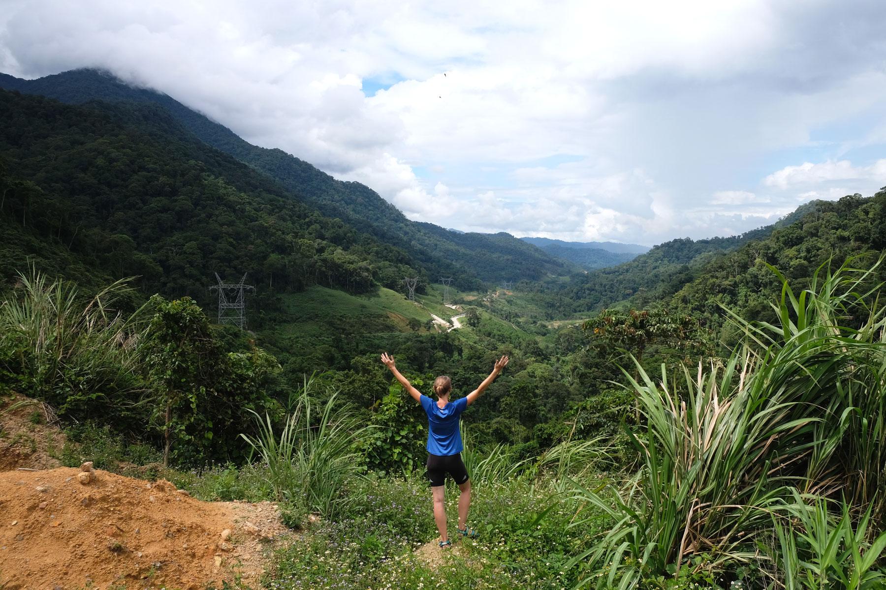 Leo trägt Fahrradkleidung und blickt auf ein grünes Tal in Vietnam.