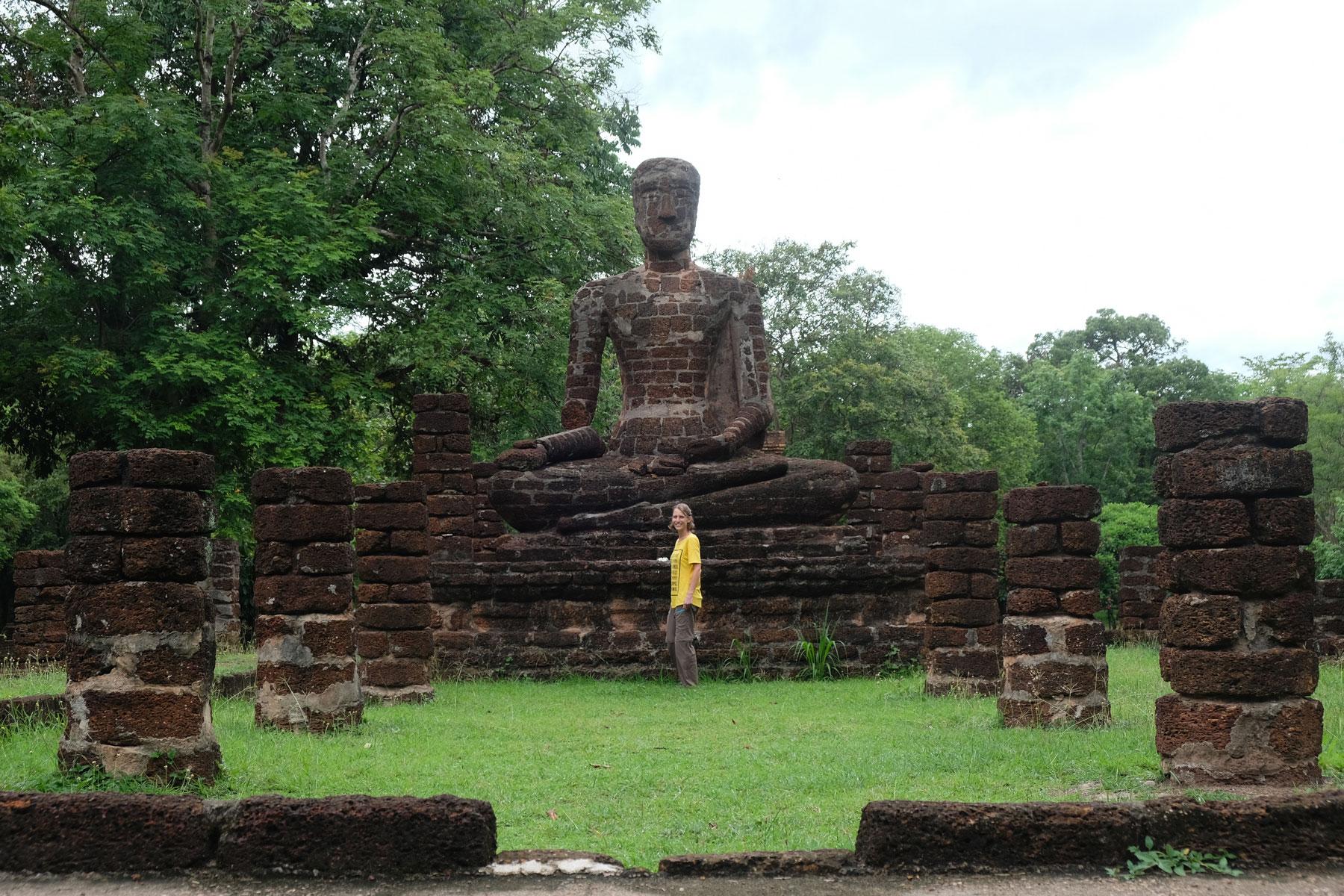 Leo steht in Kamphaeng Phet vor einer großen sitzenden Buddhastatue aus Stein.