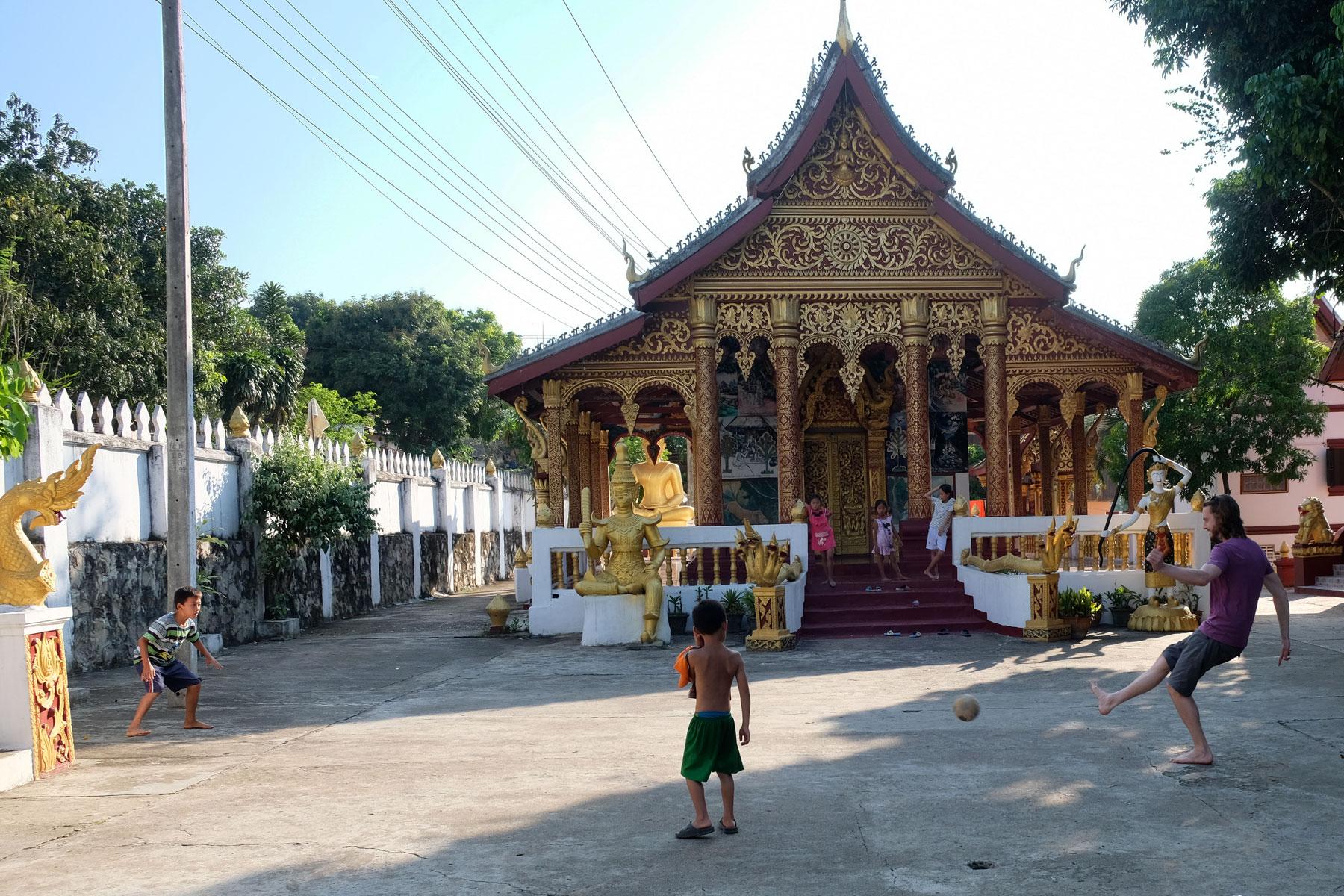 Sebastian spielt vor einem laotischen Tempel mit Kindern Fußball.