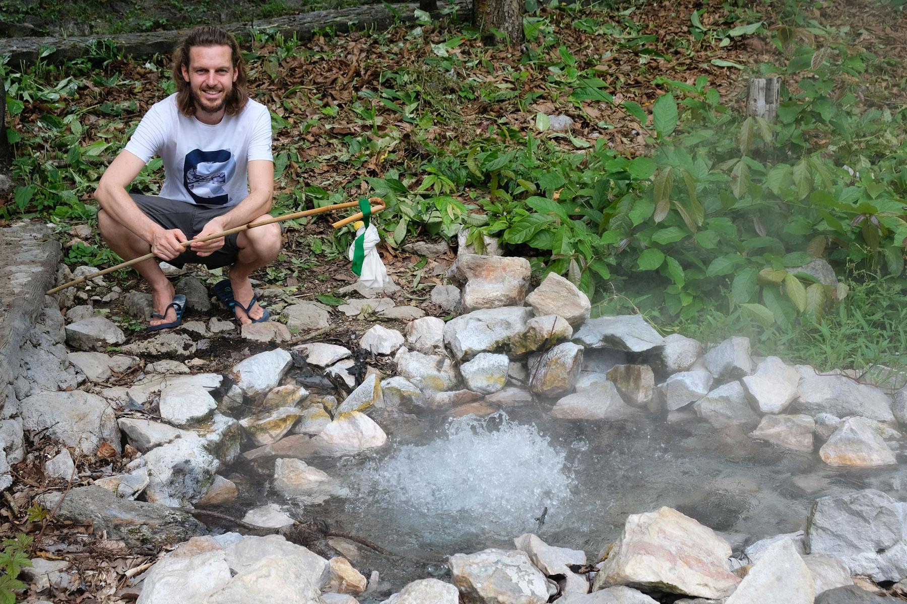 Sebastian kocht mit Hilfe eines Stoffbeutels und eines Stocks Eier im kochenden Wasser des Pong Duet Geysirs.