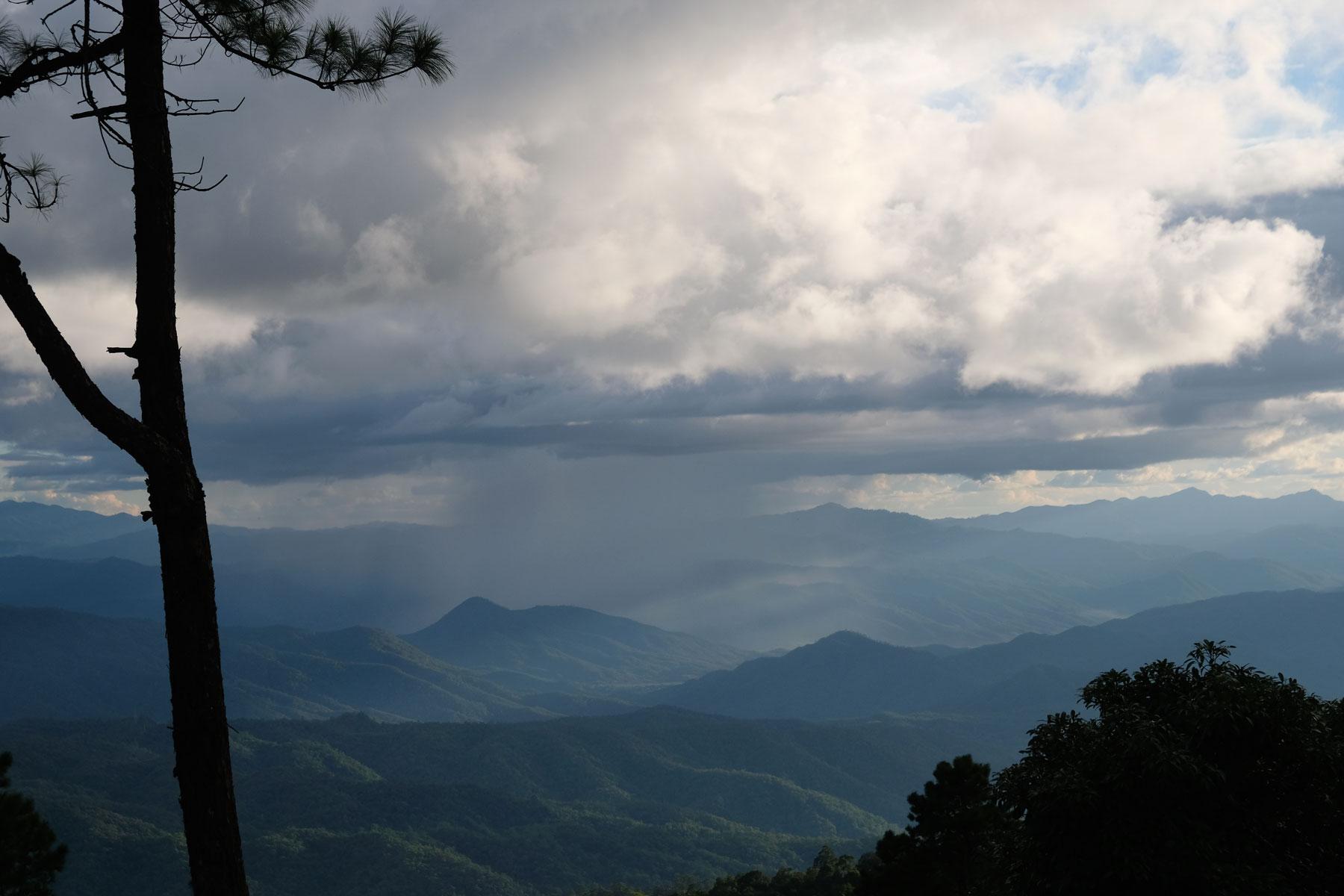 Dunkle Regenwolken ziehen über die Berge eines thailändischen Nationalparks.