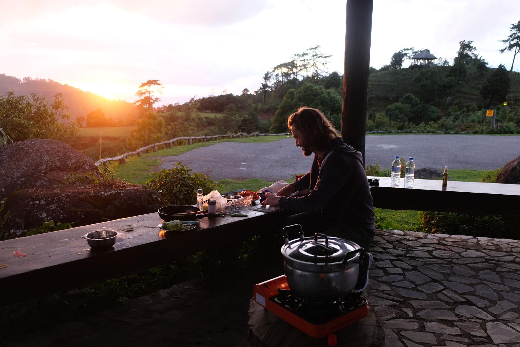 Sebastian kocht im Licht der untergehenden Sonne.