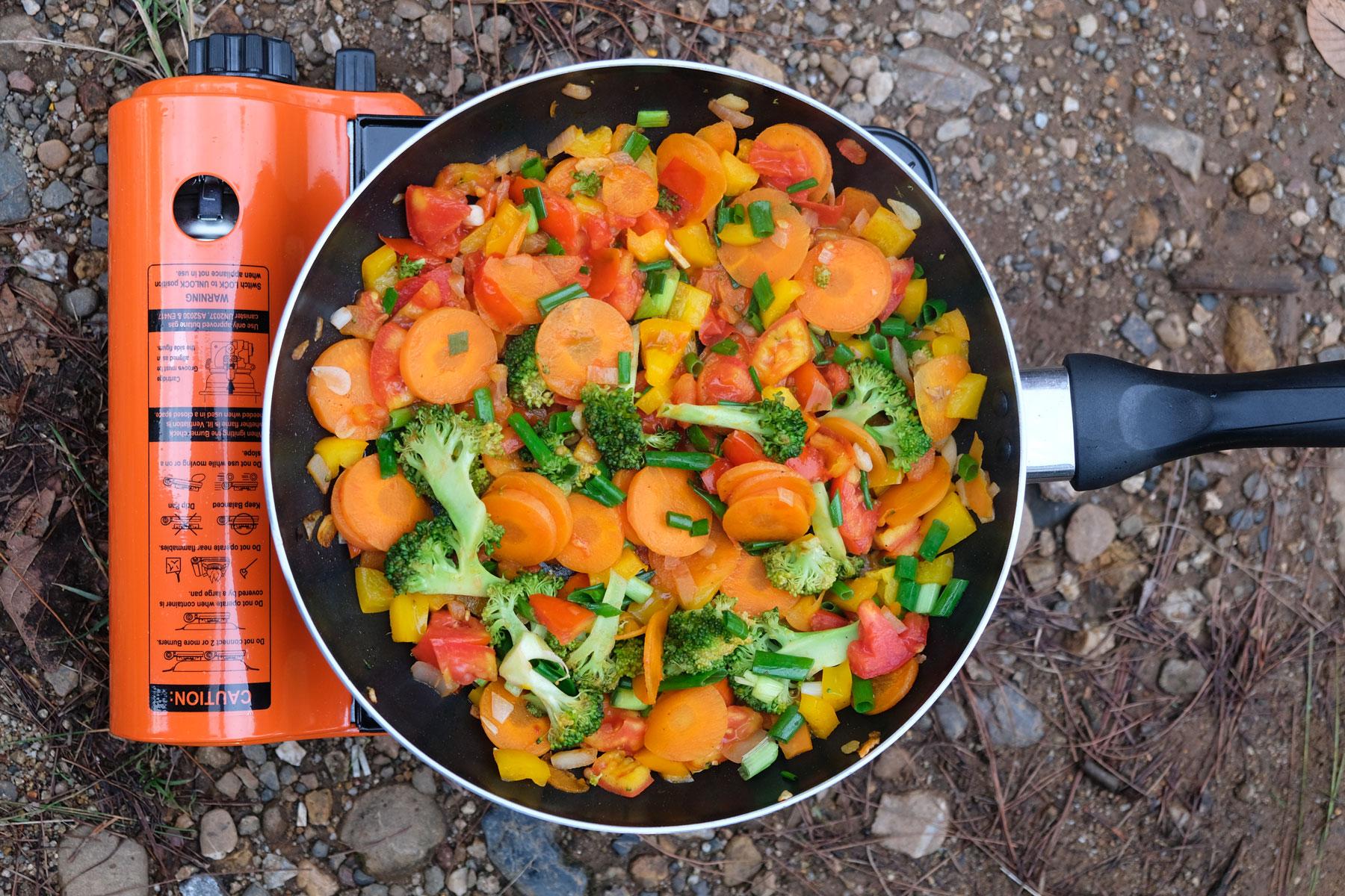 Eine Pfanne mit buntem Gemüse auf einem Campingkocher.