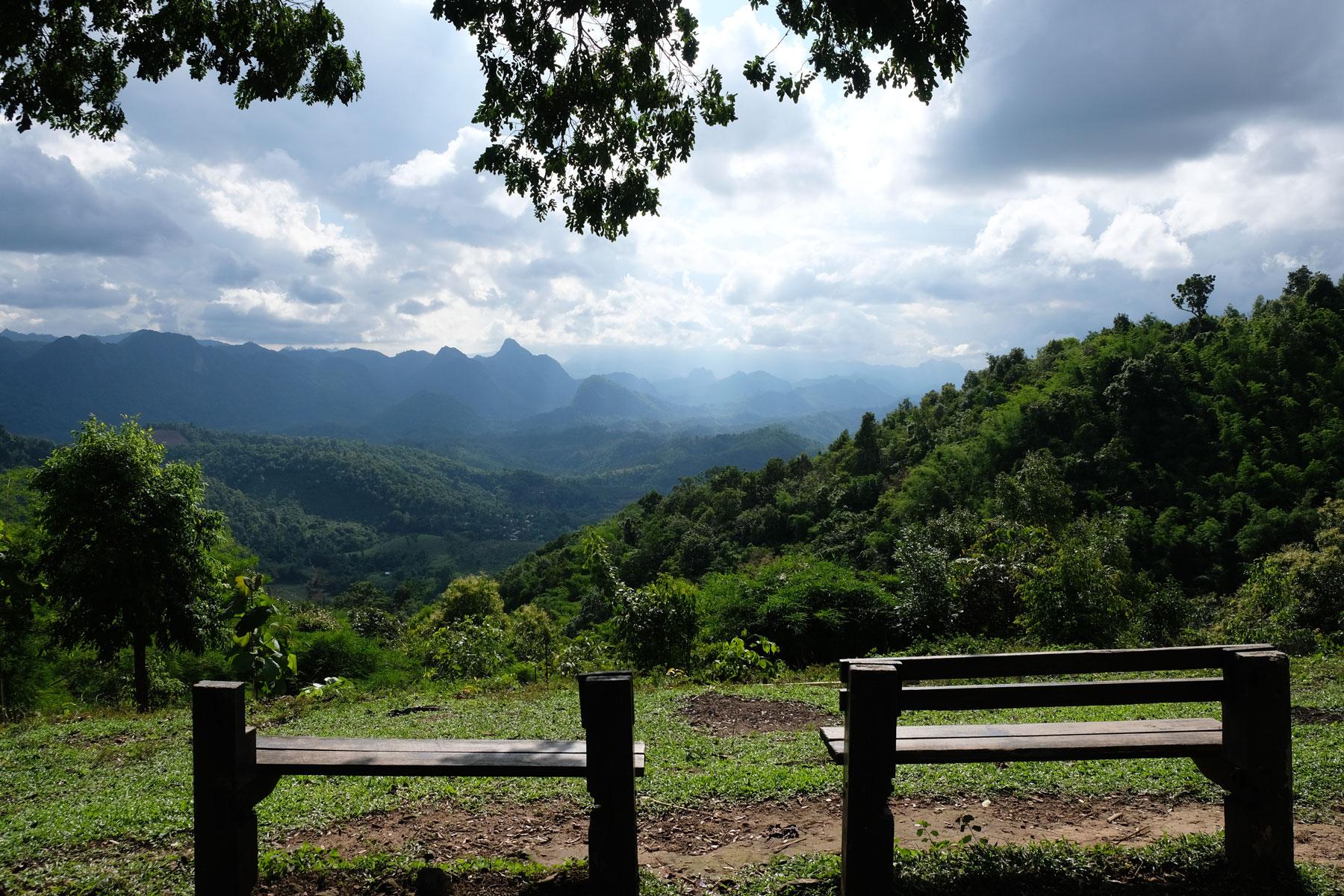 Zwei Sitzbänke stehen oberhalb von bewaldeten Bergen in einem Nationalpark in Thailand.