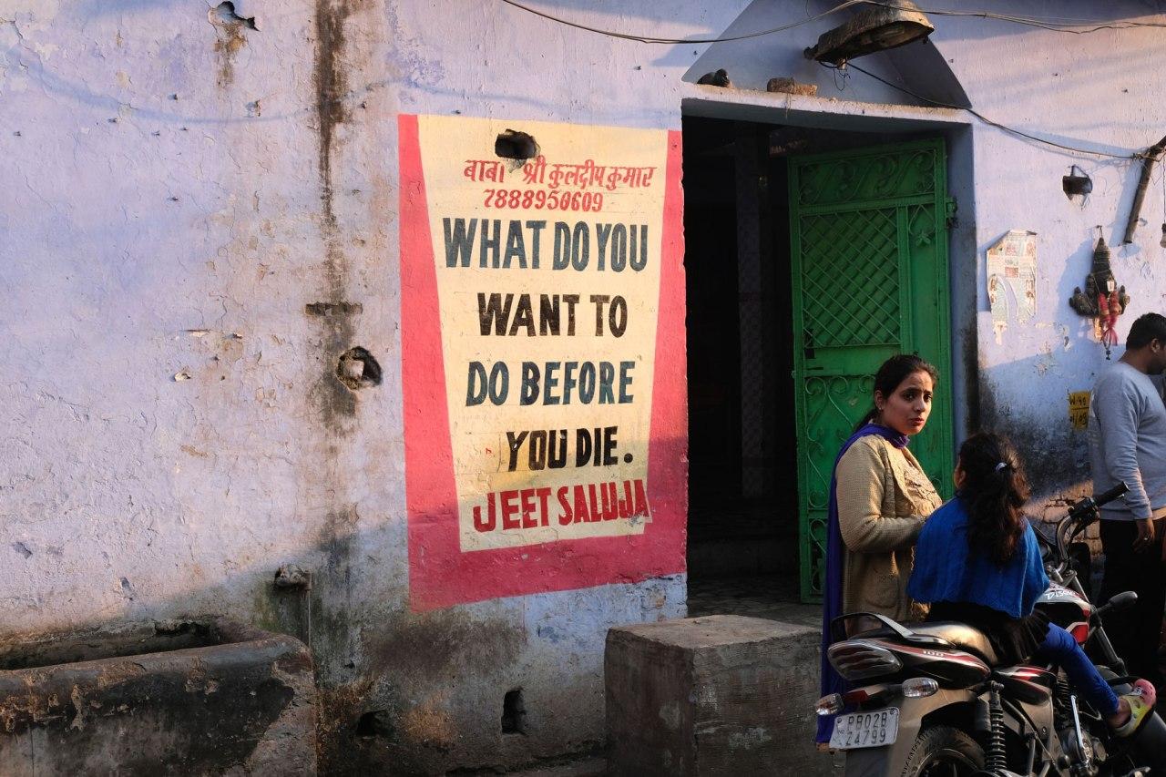 Indische Frauen vor einem Plakat, das die Frage aufwirft, was man vor dem eigenen Tod noch machen möchte.