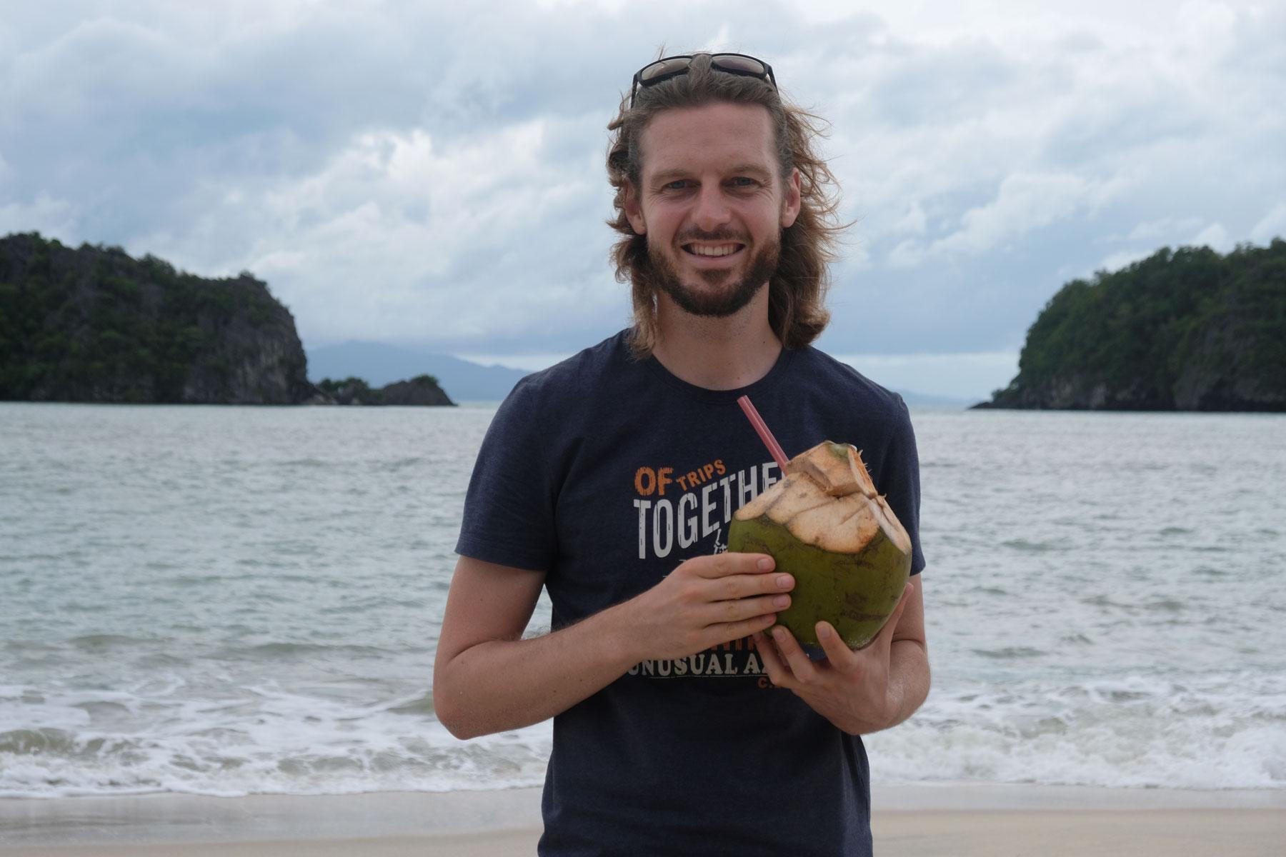 Sebastian steht mit einer Kokosnuss am Strand von Pantai Tanjung Rhu.