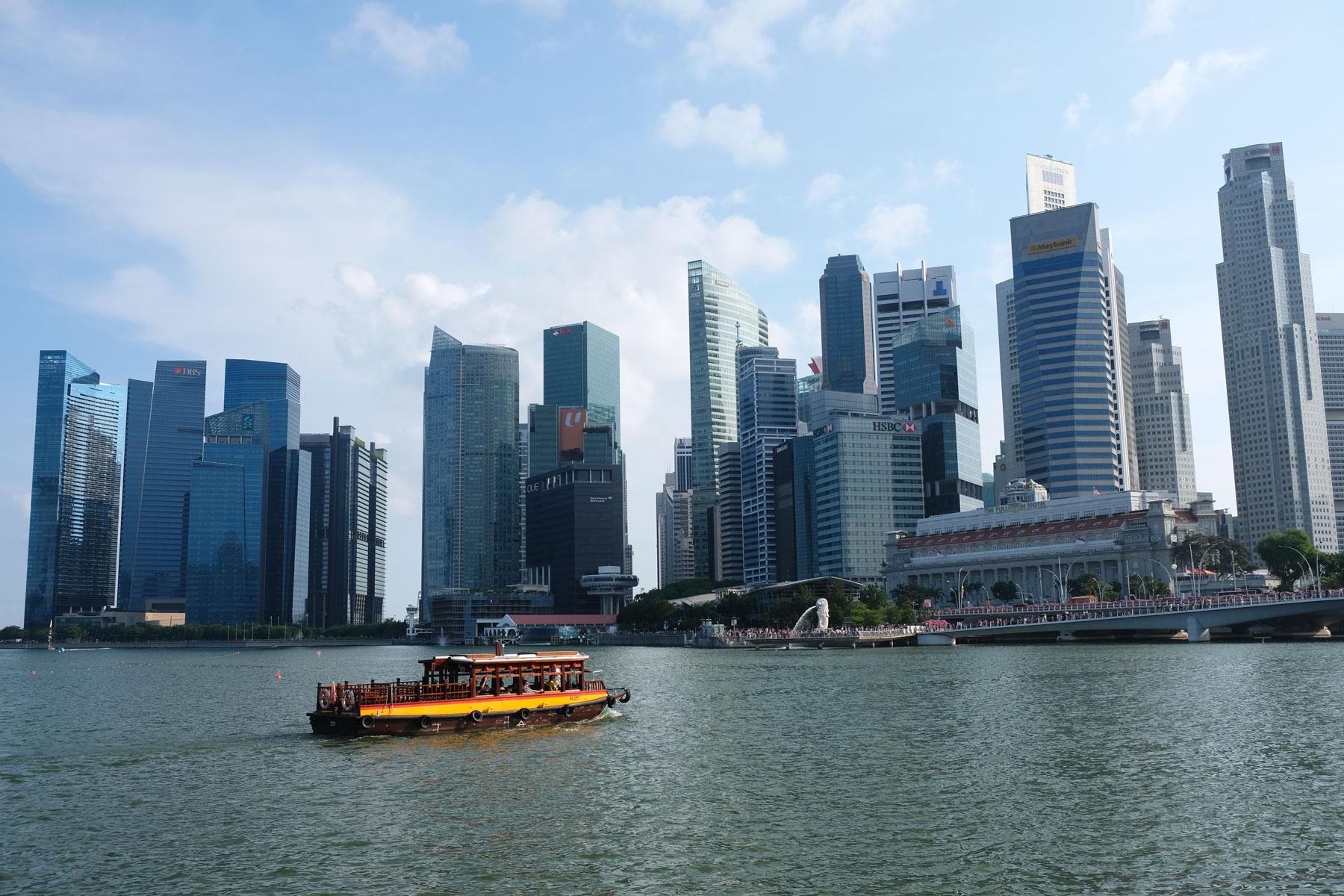 Ein gelbes Schiff vor der Skyline Singapurs.