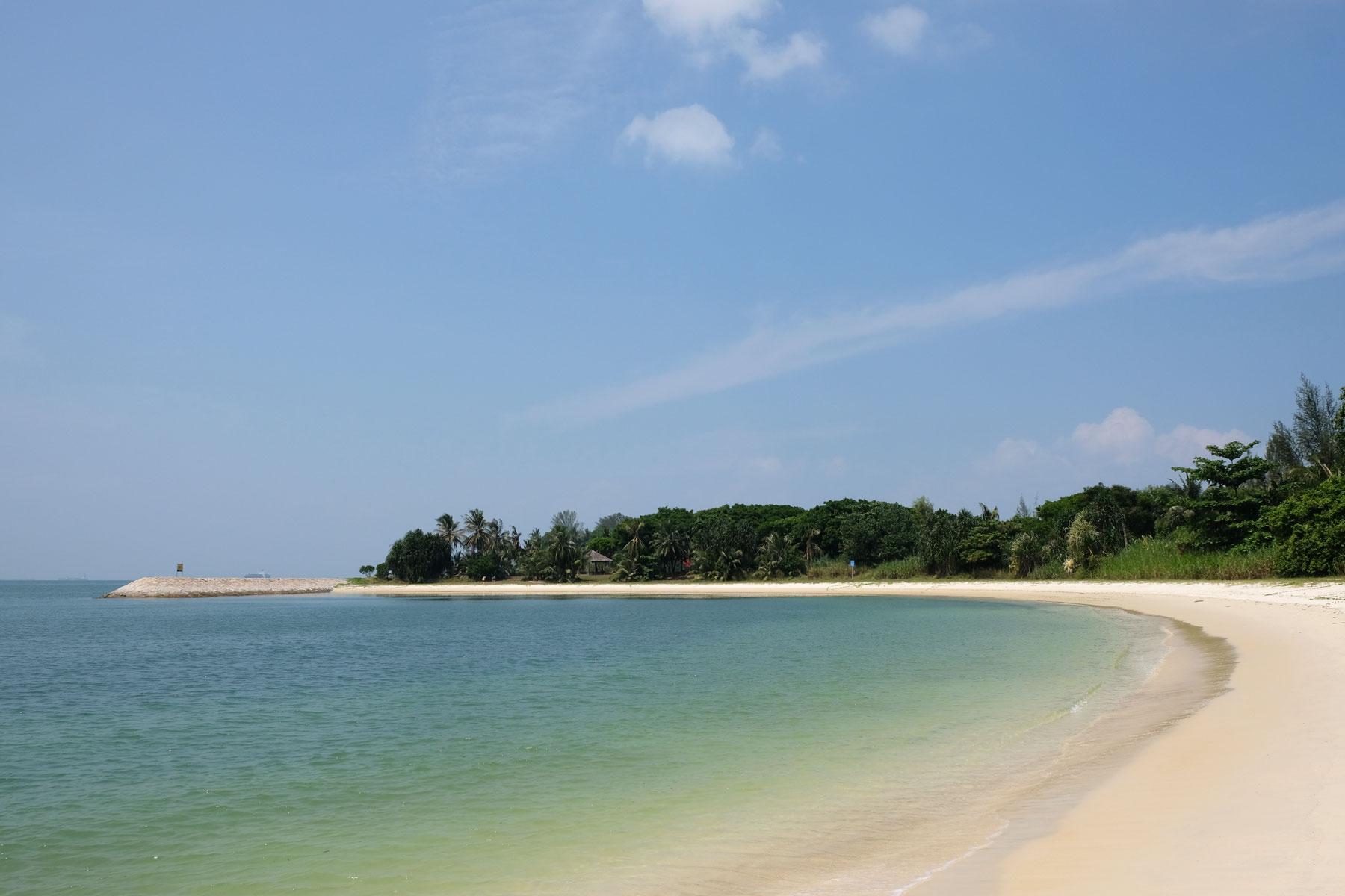 Ein Sandstrand an blau-grünem Wasser