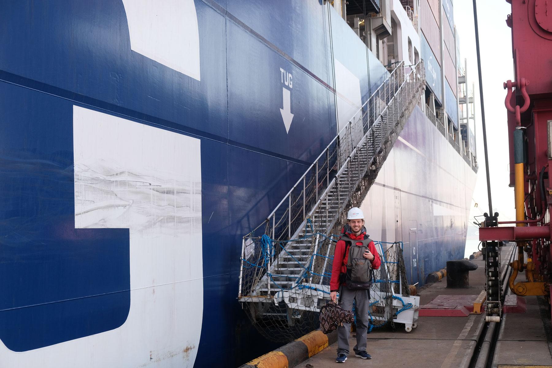 Sebastian steht vor unserem beeindruckend großen Schiff Jacques Jospeh, hinter ihm ist die Gangway zu sehen.