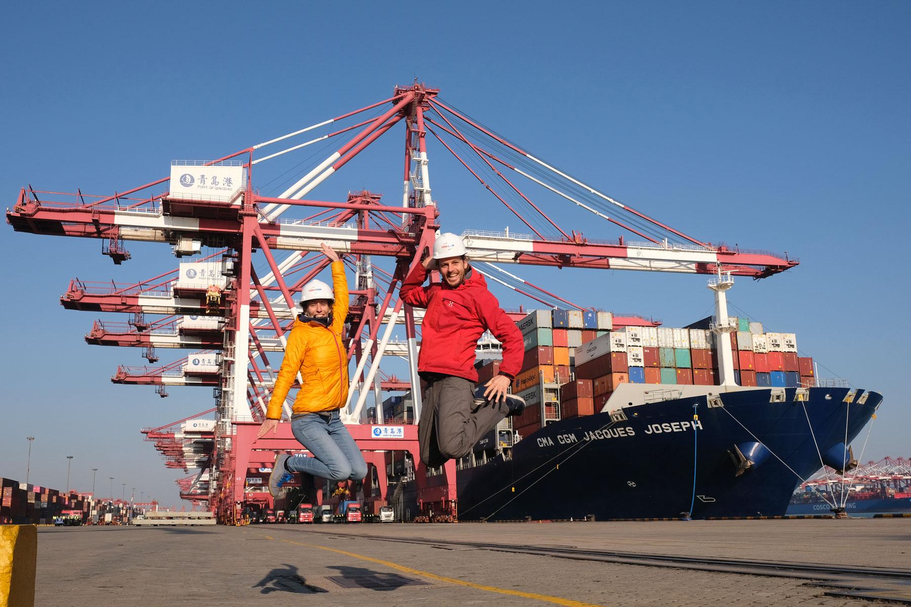 Leo uns Sebastian springen am Hafen von Qingdao vor dem Containerschiff Jacques Joseph in die Luft.