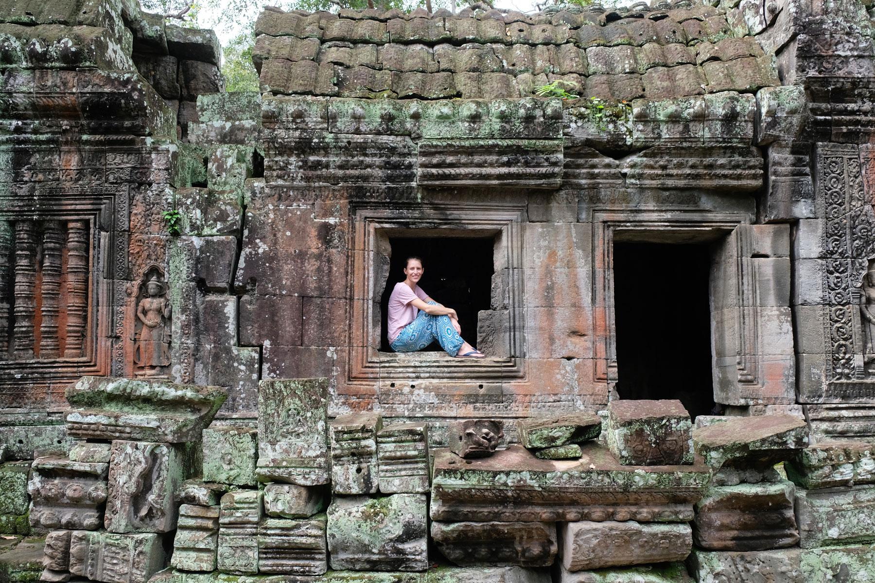 Leo sitzt in einem Fenster des Tempels Banteay Kdei
