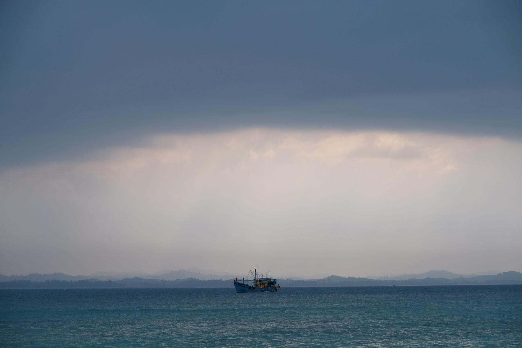 Ein Schiff schaukelt unter dunklen Wolken auf dem Meer