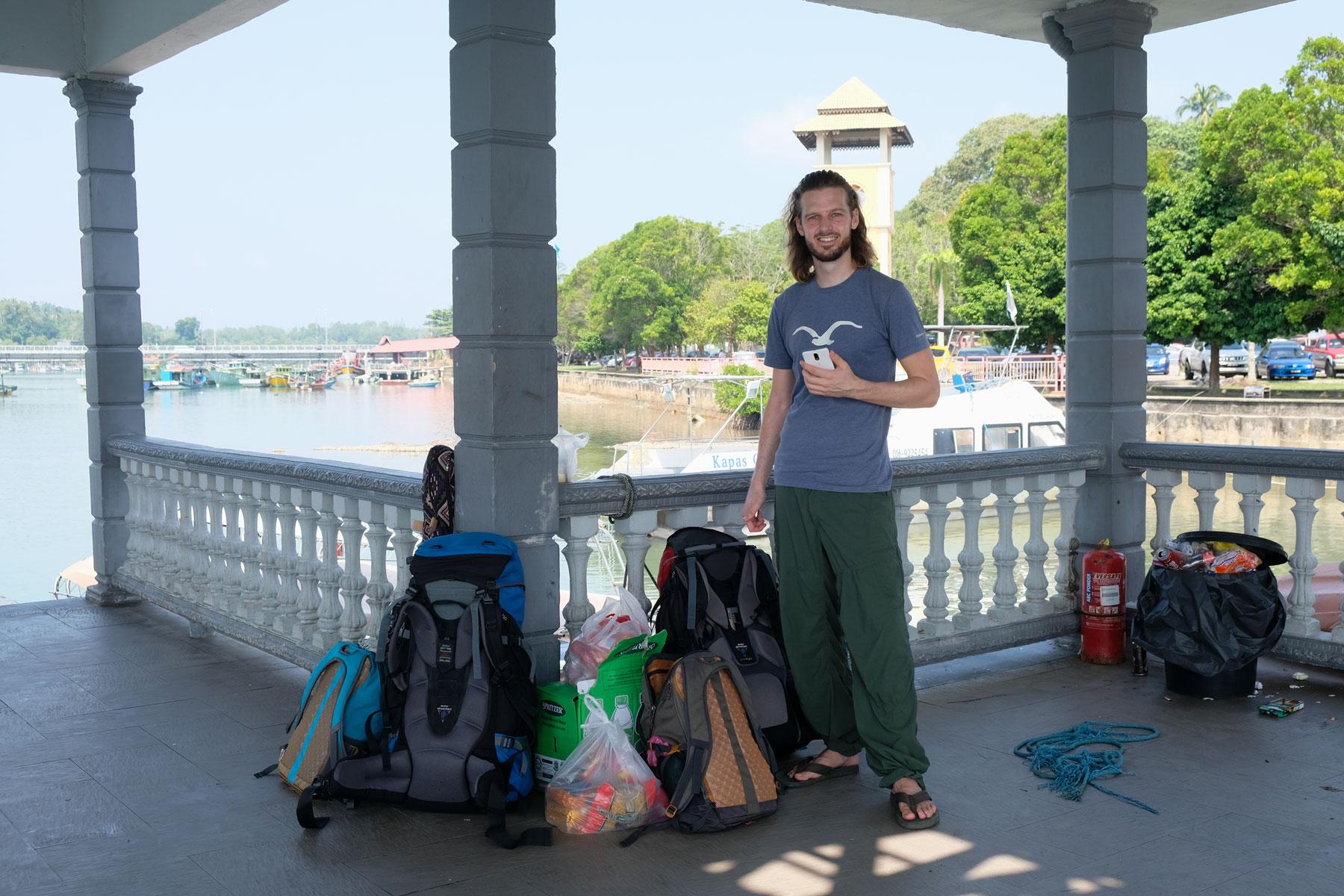 Sebastian steht neben unserem Gepäck am Fähranleger von Marang