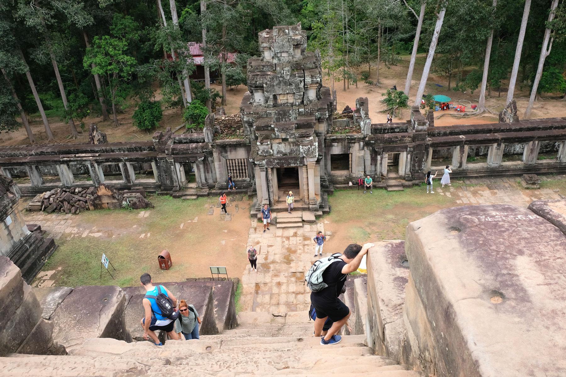 Menschen laufen vorsichtig die extrem steilen und schmalen Stufen des Tempels Ta Keo in Angkor Wat hinunter