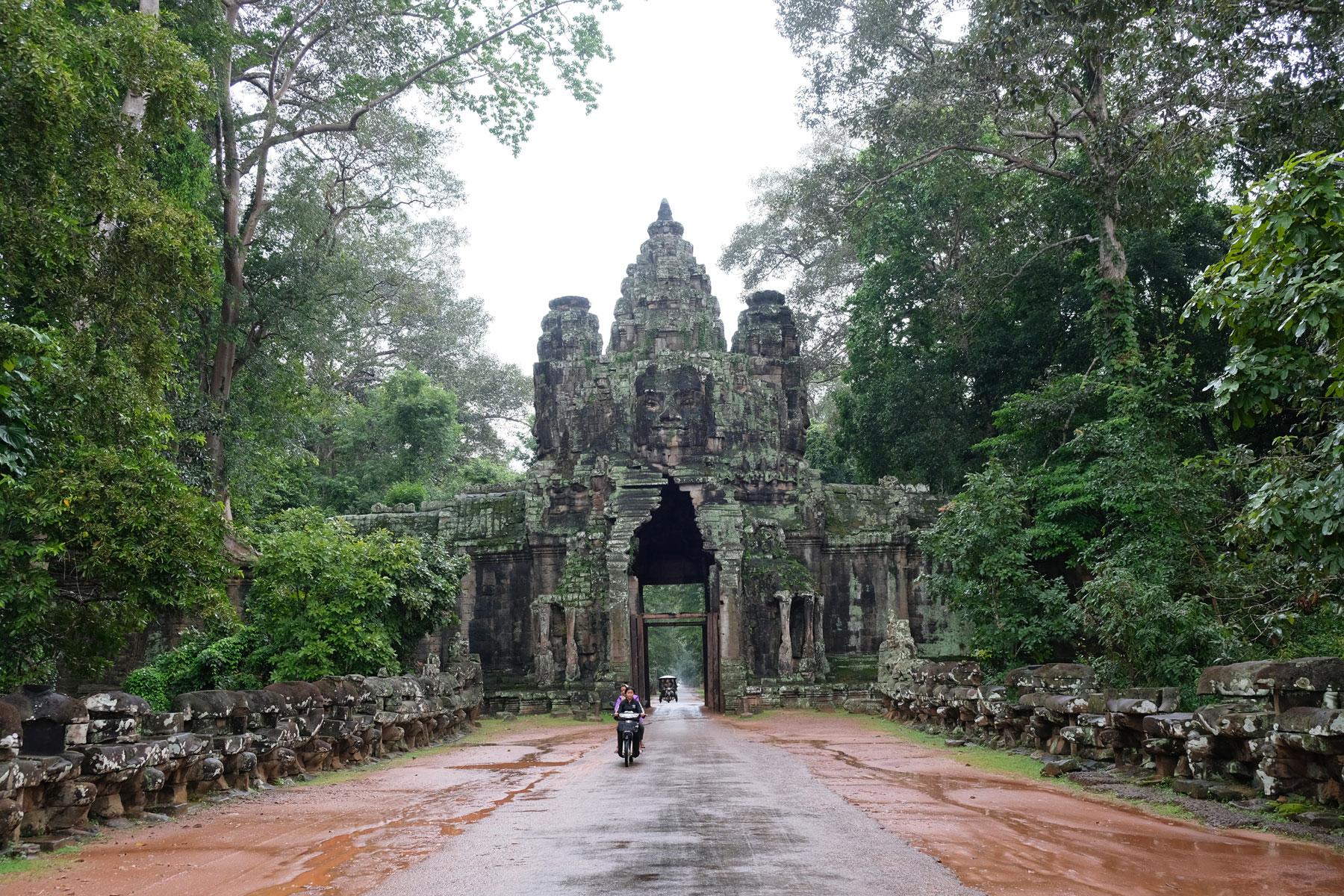 Ein Motorroller fährt aus dem Victory Gate in Angkor Wat.