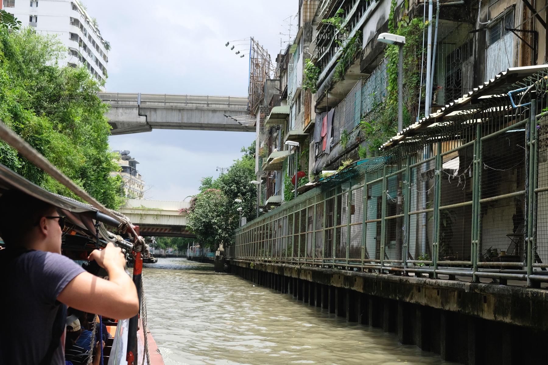 Auf einem kleinen Boot fahren wir direkt an den Häusern der Einheimischen Bangkoks vorbei.