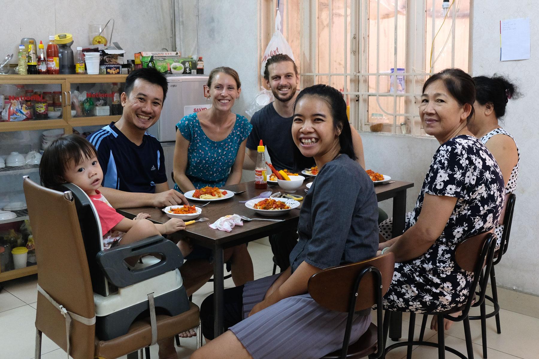 Leo und Sebastian sitzen mit ihren vietnamesischen Couchsurfing-Gastgebern am Esstisch.