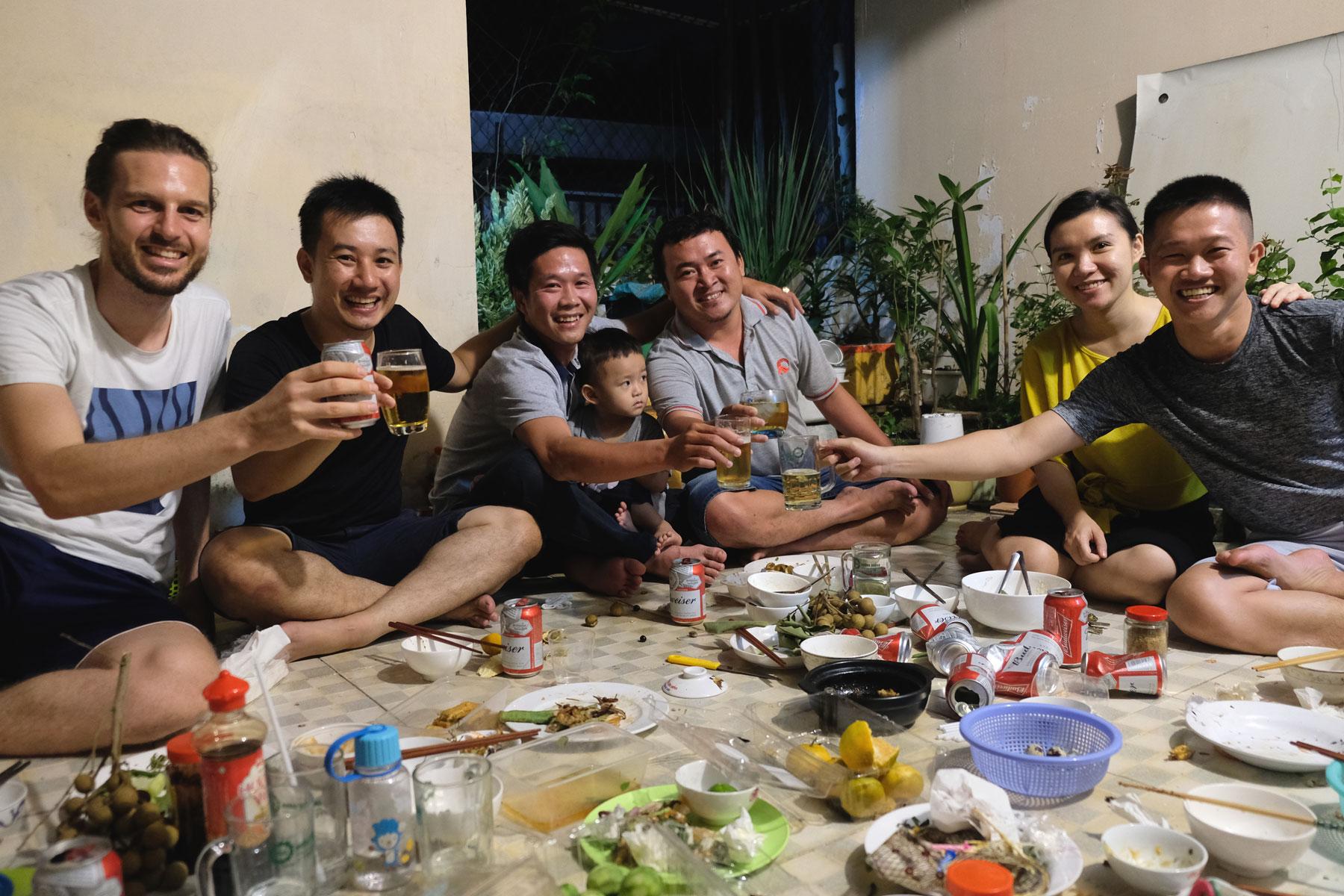 Sebastian sitzt mit Couchsurfing-Gastgeber Hanh und dessen Freunden auf dem Boden und stößt zu Ehren von Hanhs Geburtstag mit ihnen an.