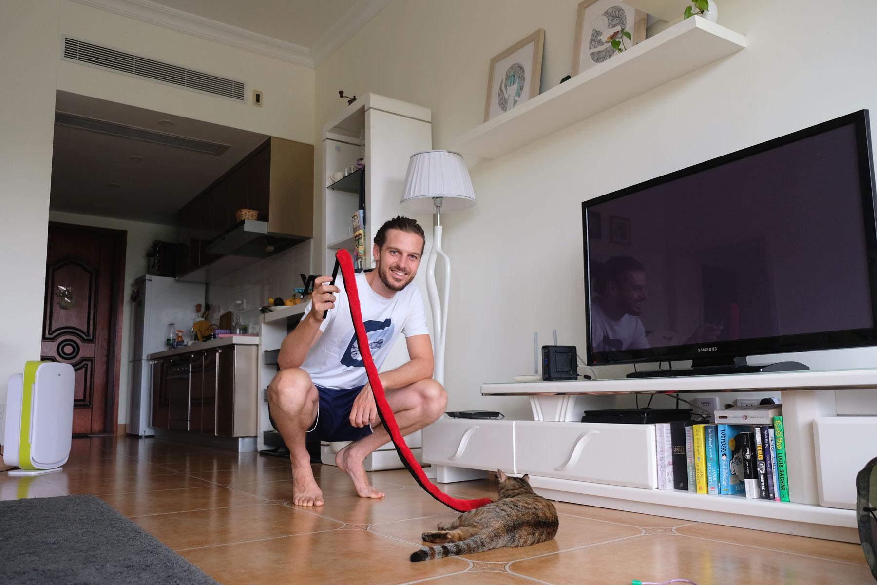 Sebastian spielt beim House Sitting in China mit einer Katze im Wohnzimmer.