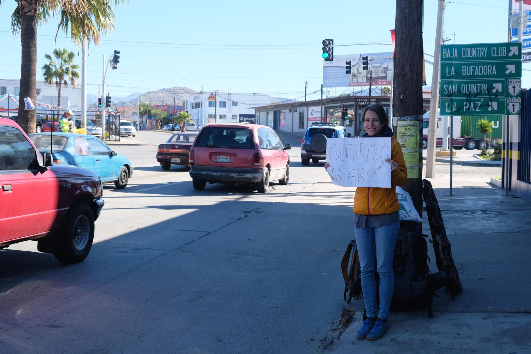 Leo steht mit einem Schild am Straßenrand in Ensenada und versucht zu trampen.