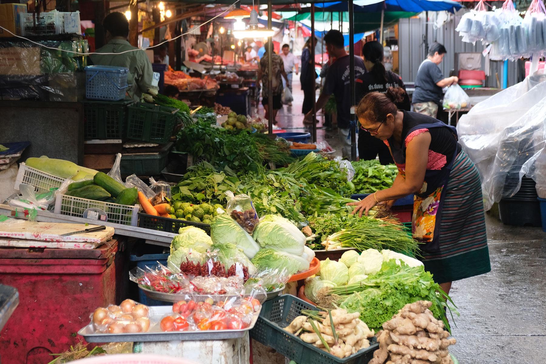 Eine Frau sortiert auf einem Markt in Bangkok ihr Gemüse.