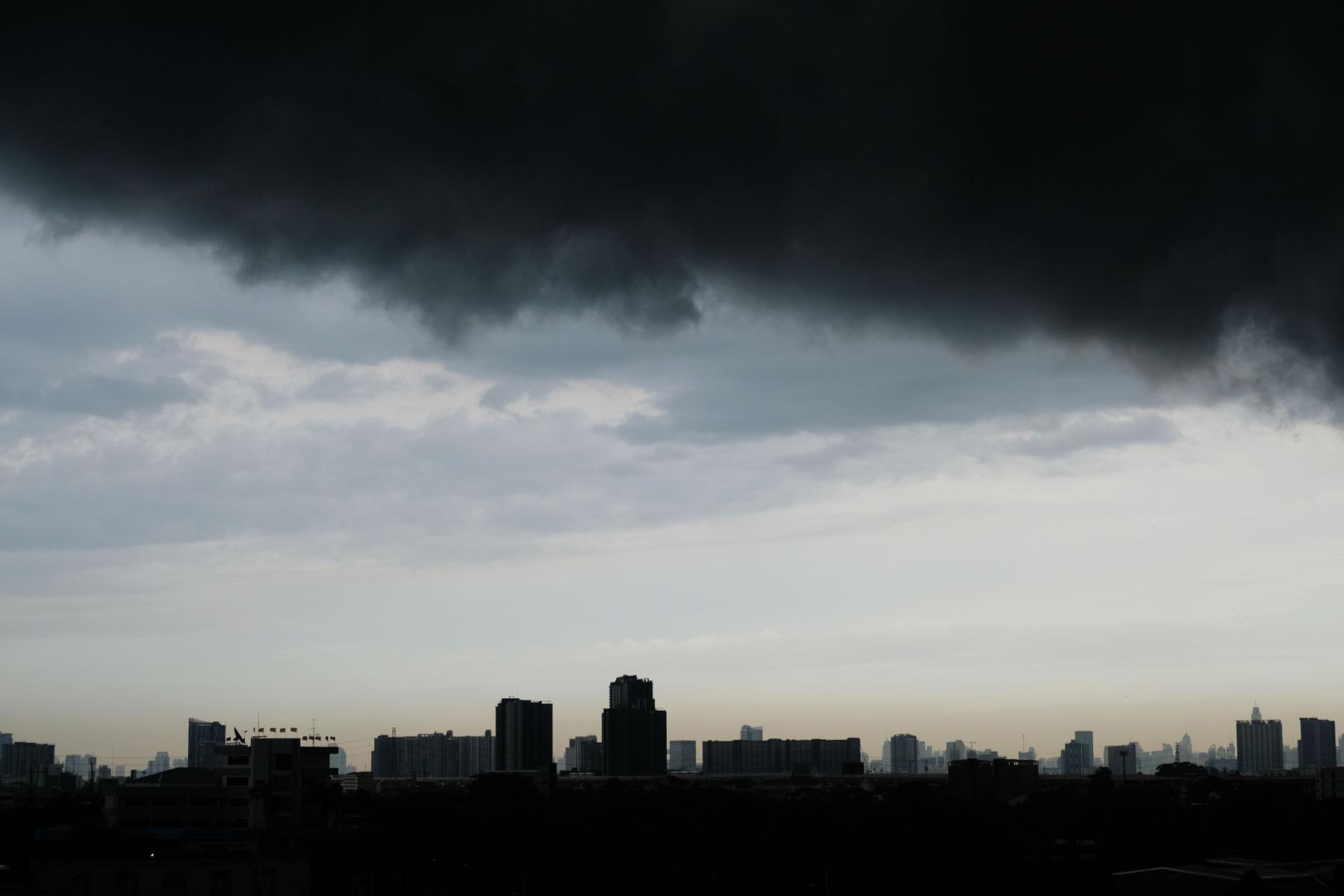 Eine schwarze Monsunwolke hängt bedrohlich über Bangkok.
