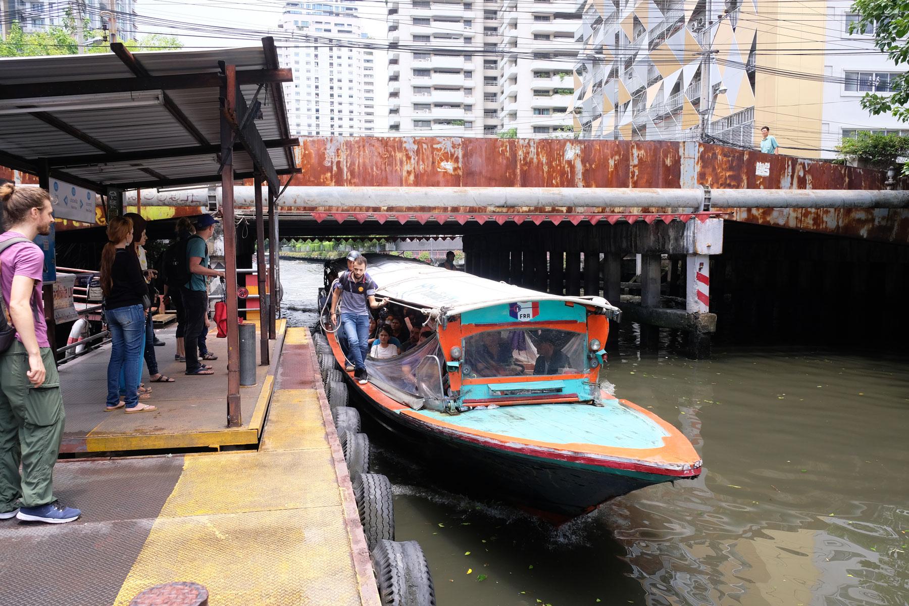 Sebastian steht am Pier und wartet auf das Anlegen des kleinen Schiffs, mit dem wir durch die Kanäle Bangkoks fahren werden.
