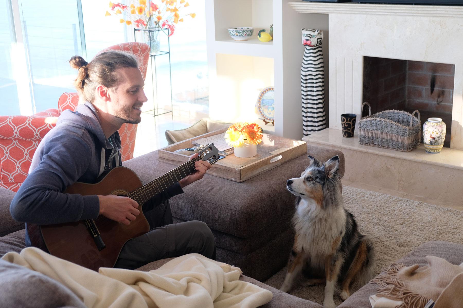 Sebastian spielt Hund Ellie ein Lied auf der Gitarre vor. Sie hört gespannt zu.
