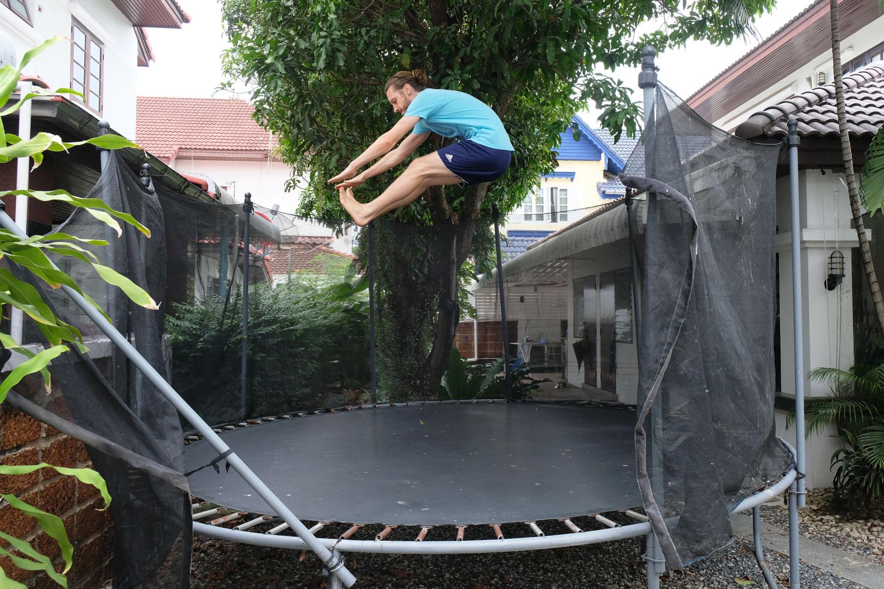 Sebastian hüpft auf dem großen Trampolin im Garten unseres Hauses in Bangkok