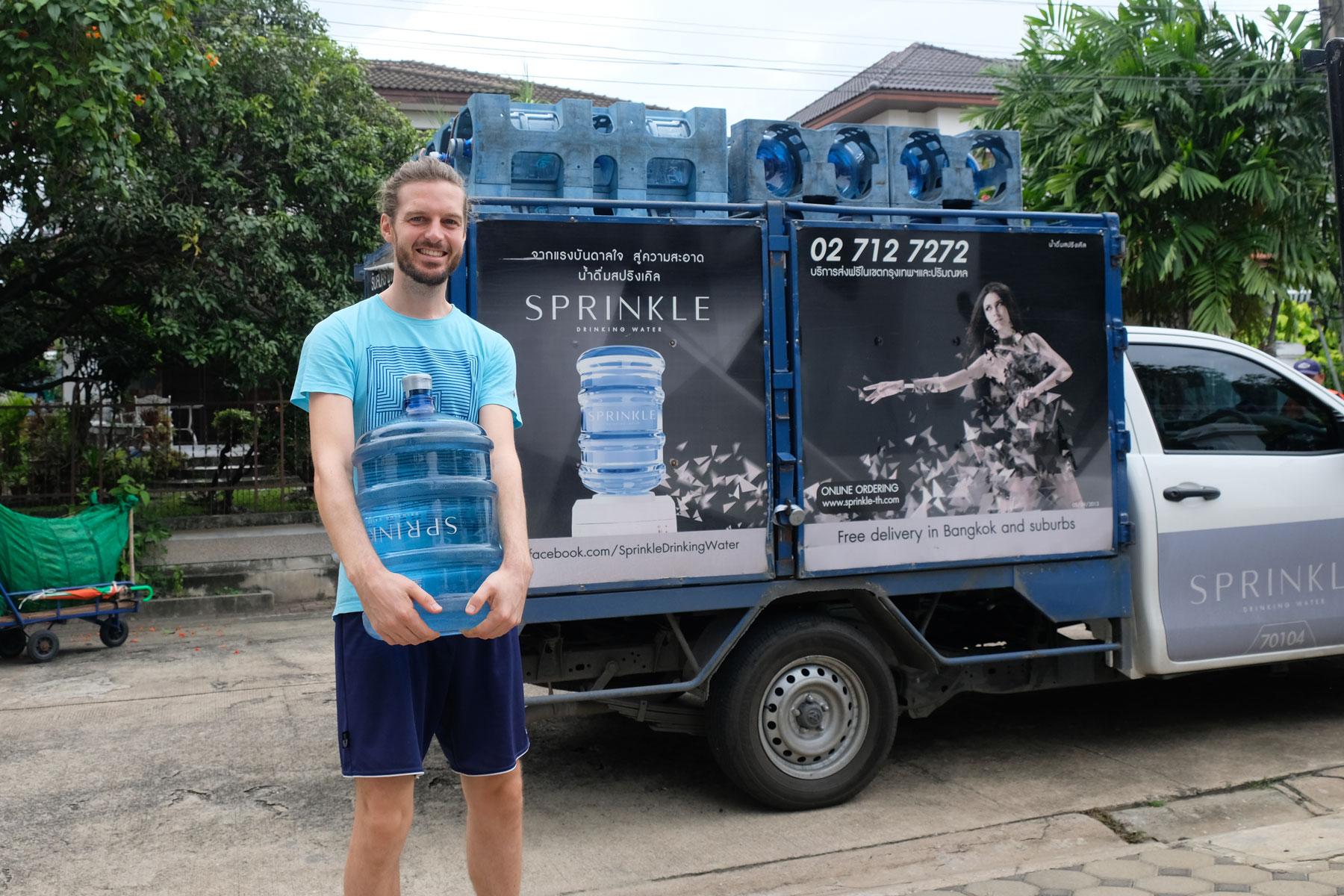 Sebastian trägt einen 20-Liter-Wasser-Kanister zum Haus.
