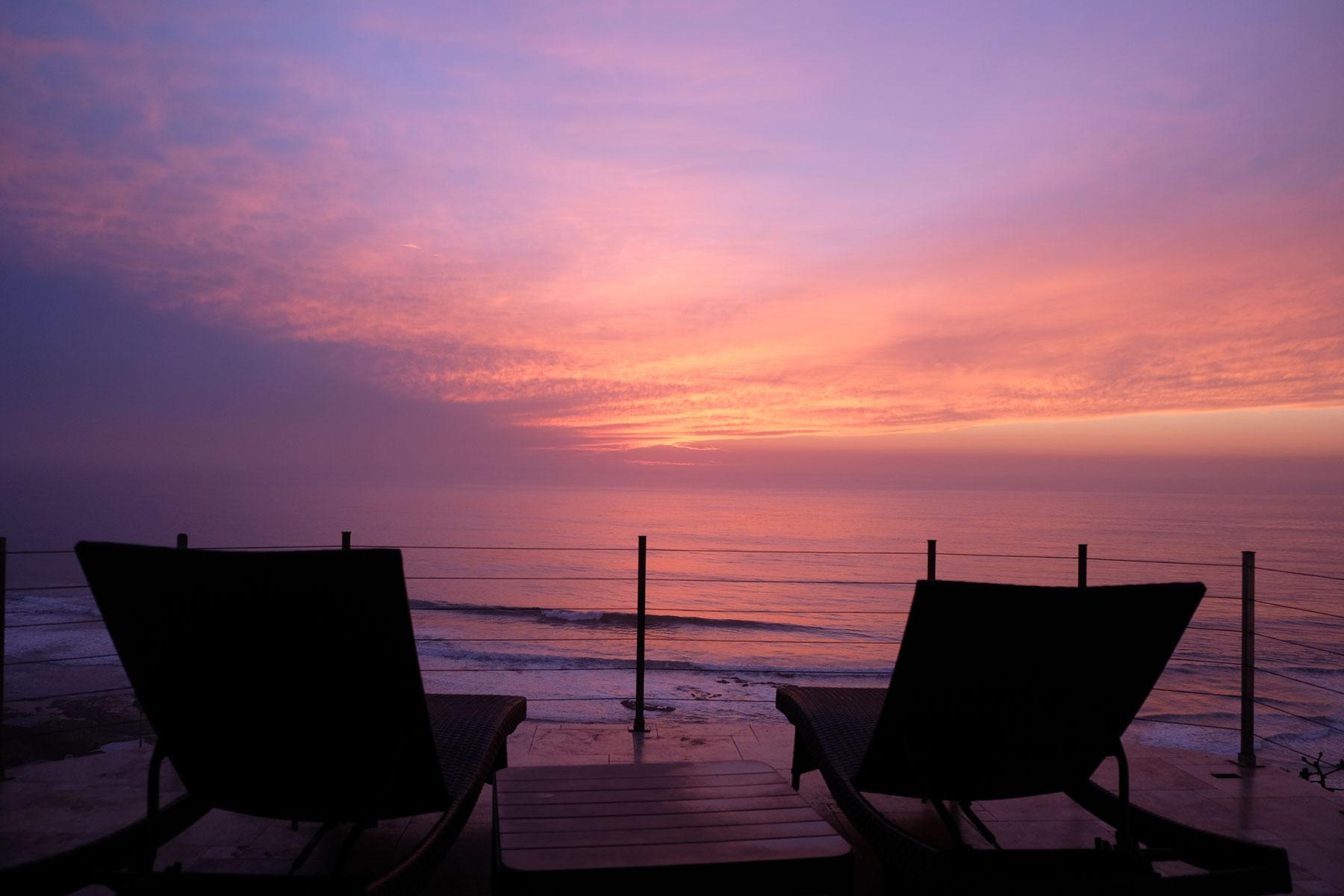 Der Himmel färbt sich lila, im Vordergrund stehen die beiden Liegestühle unserer Terasse