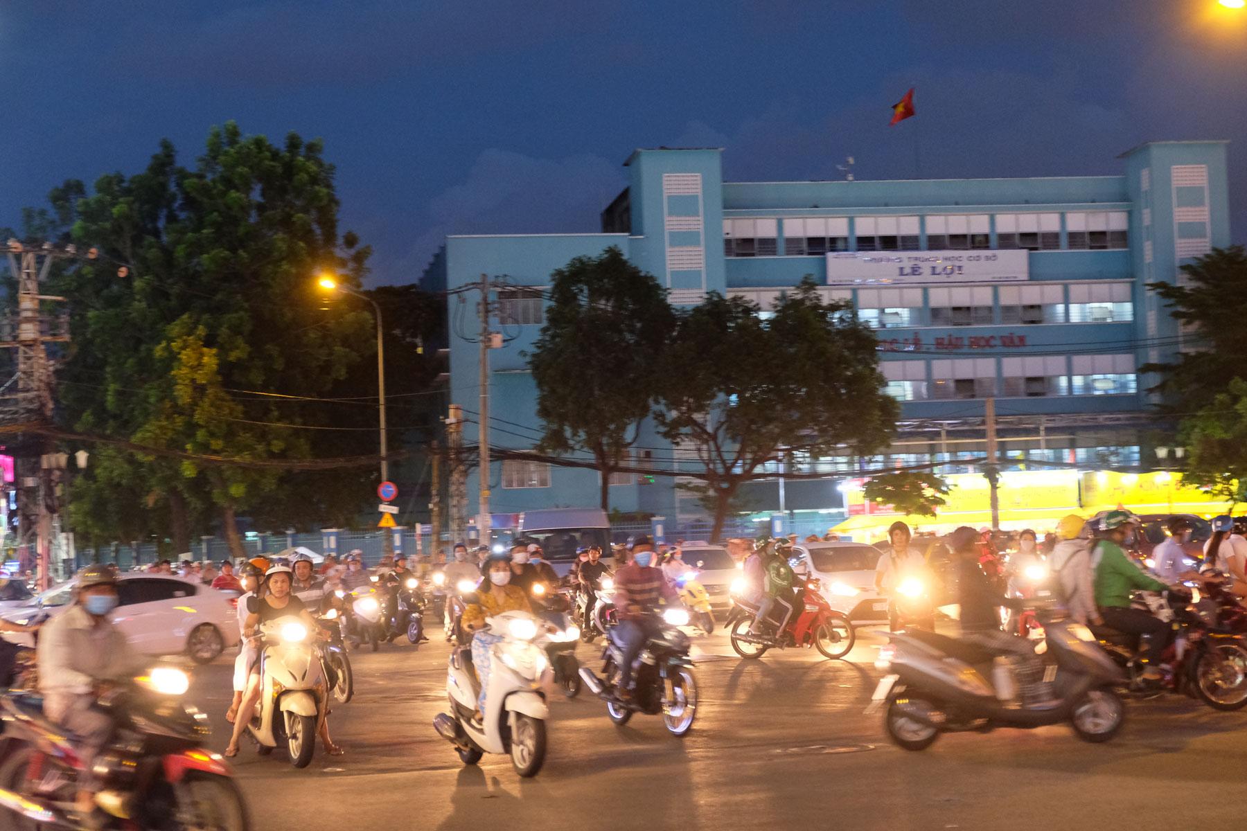 In der Dunkelheit fahren hell beleuchtete Motorroller durch die Innenstadt von Ho-Chi-Minh-City in Vietnam.