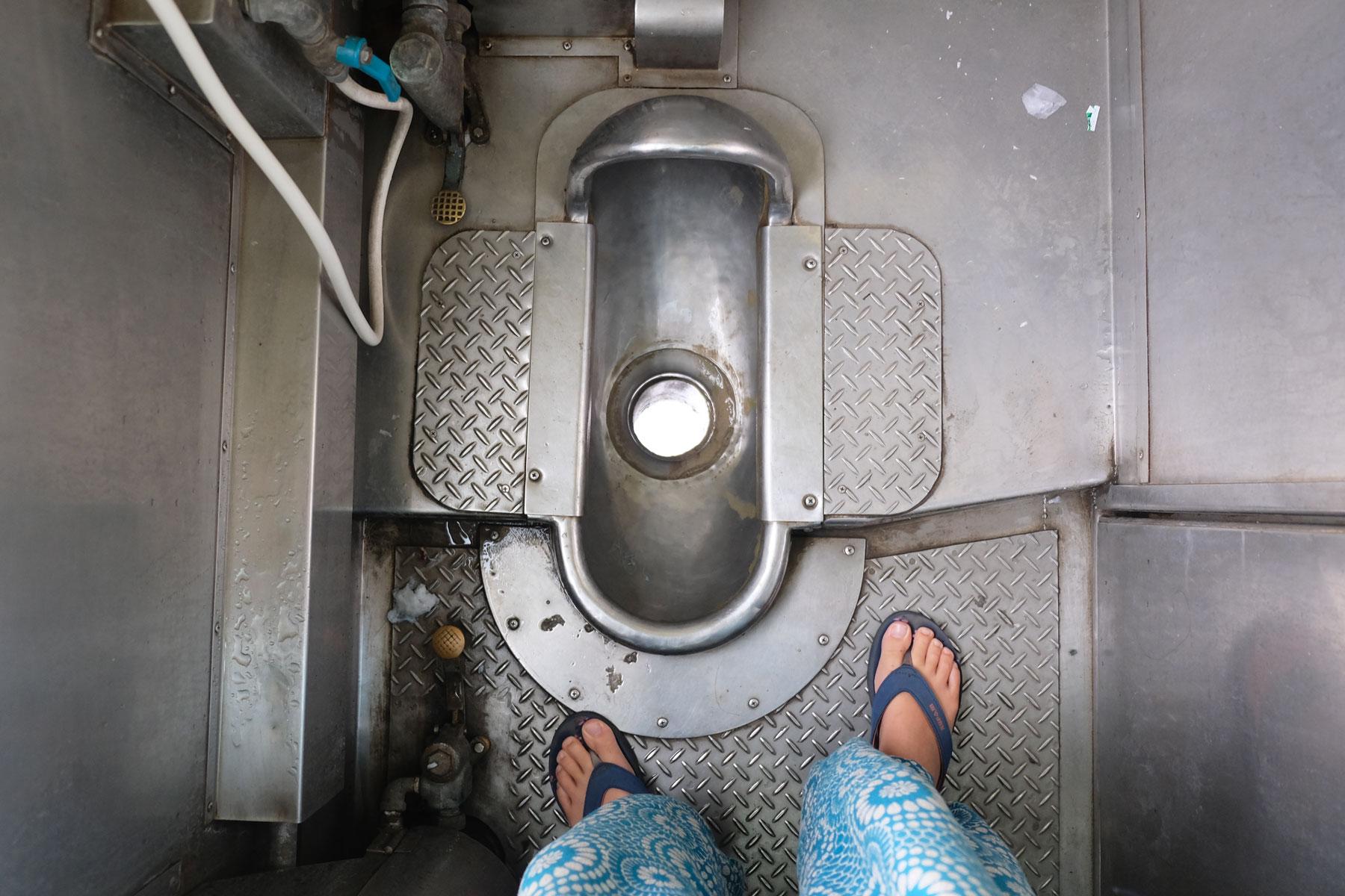 Leo schaut von oben auf ein Hochklo im Zug der thailändischen Bahn.