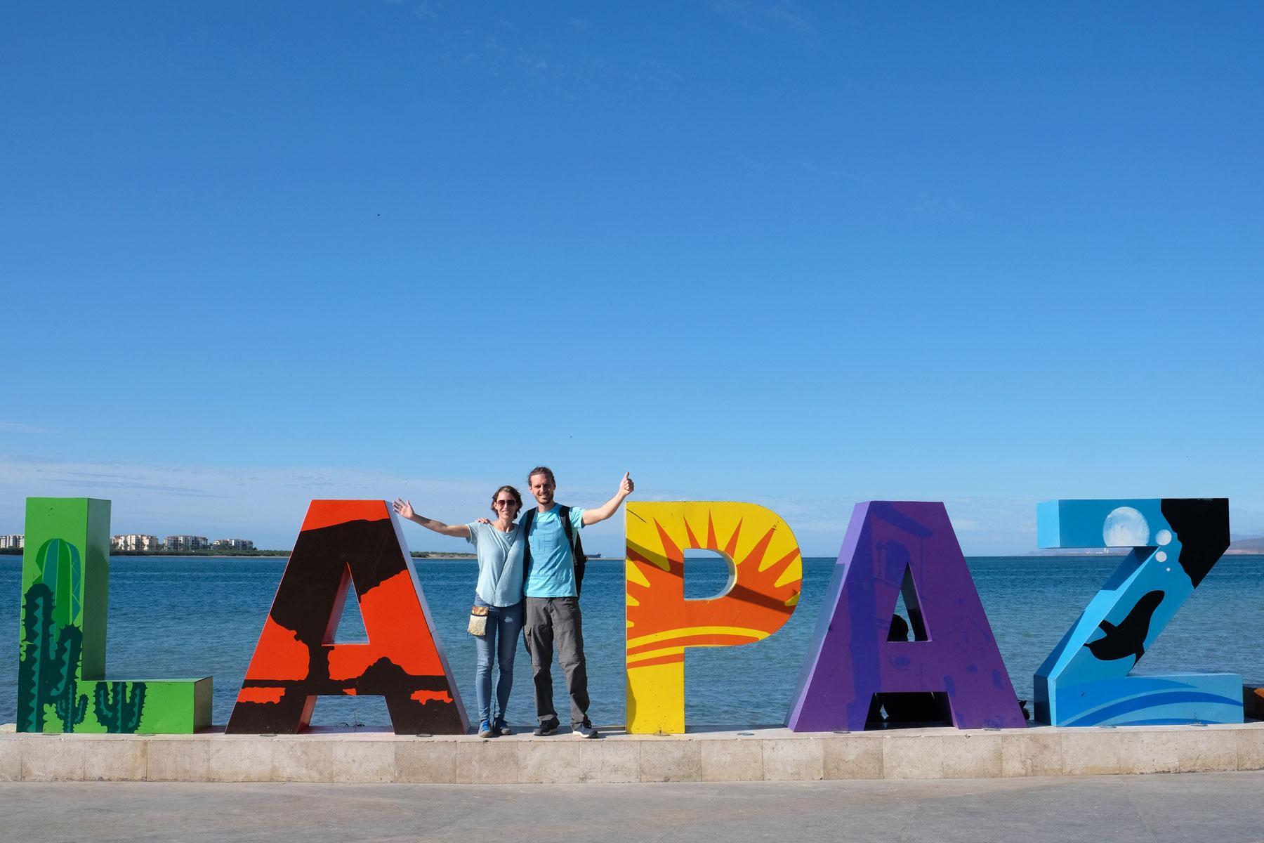 """Leo und Sebastian stehen zwischen großen Buchstaben, die den Namen """"La Paz"""" schreiben."""