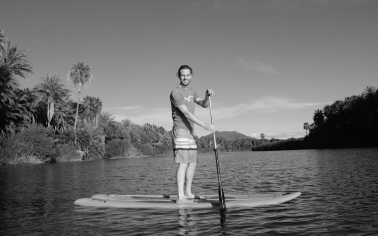 Sebastian steht auf einem Standup-Board auf dem Fluss von San Ignacio, Baja California, Mexiko.