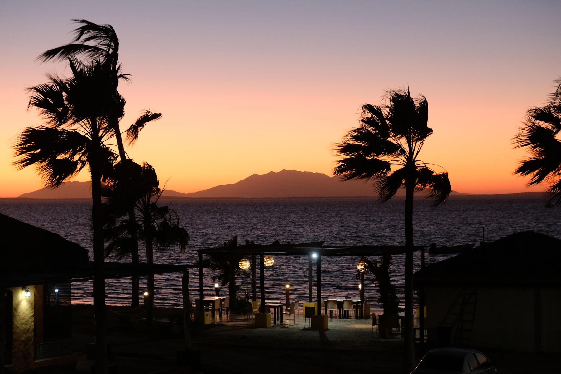 Palmen und eine beleuchtete Bar, dahinter geht die Sonne unter.