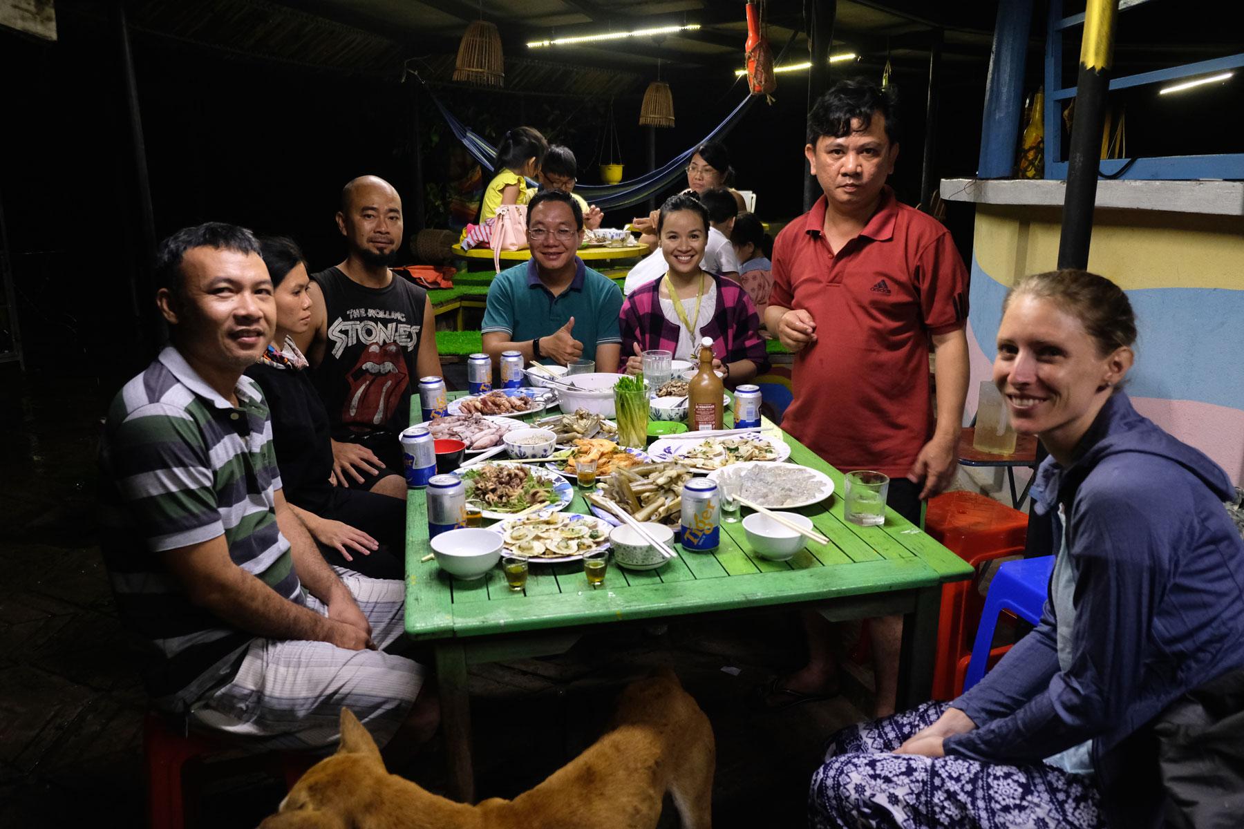 Leo sitzt mit einer Gruppe Vietnamesen am Abendessenstisch.