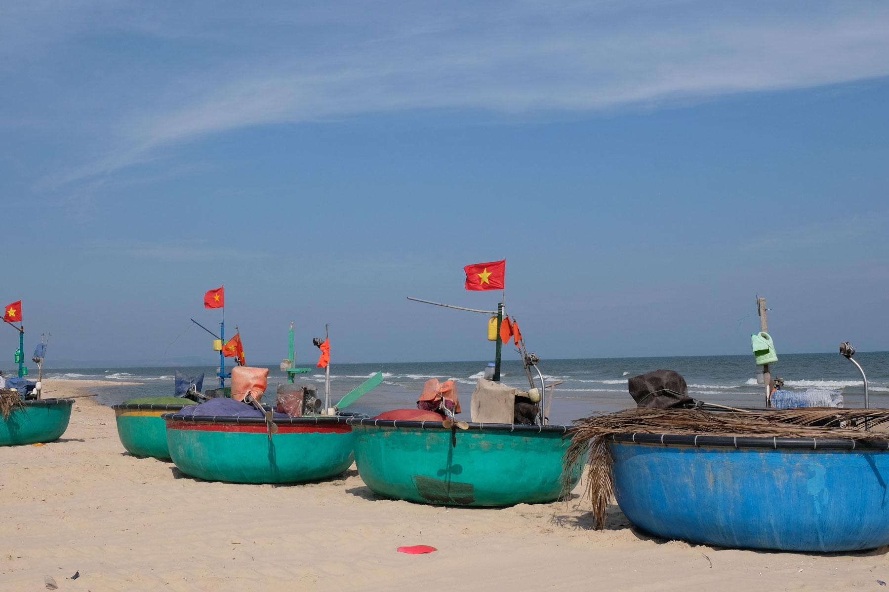 Runde Fischerboote liegen am Strand im Süden Vietnams.