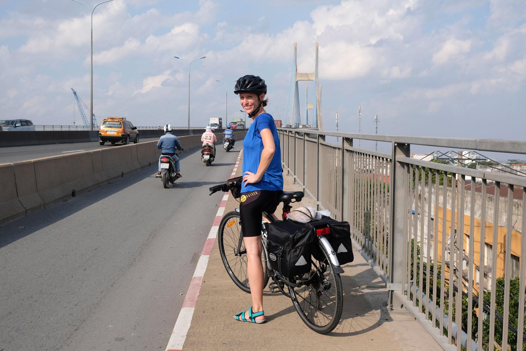 Leo steht mit ihrem Fahrrad auf der großen Brücke über den Mekong bei HCMC in Vietnam.