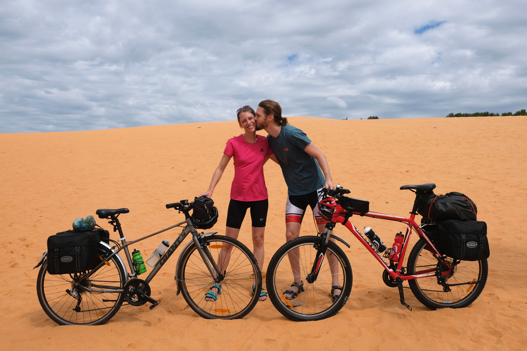 Sebastian küsst Leo auf die Wange, während sie beide mit ihren Fahrrädern auf der roten Sanddüne von Mui Ne stehen.