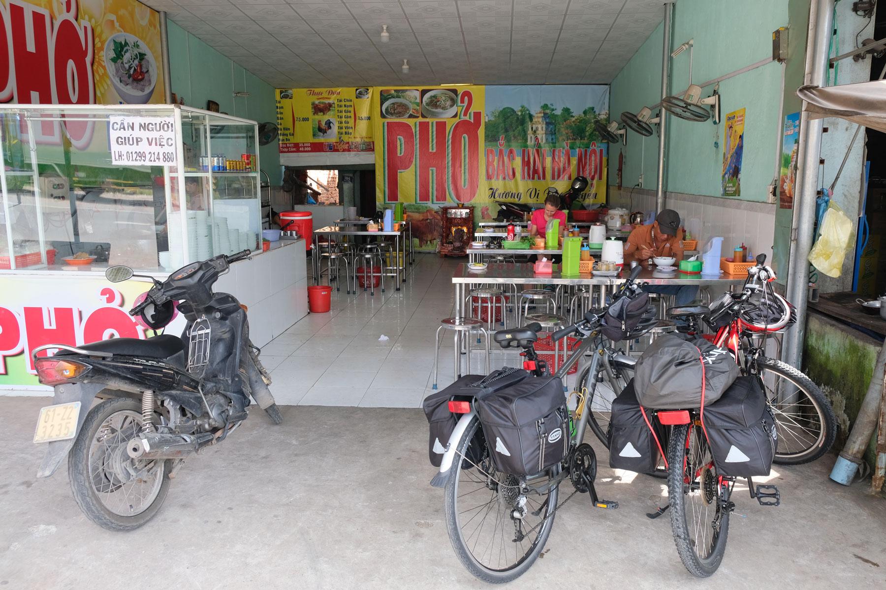 Leo sitzt in einem kleinen Pho-Restaurant, die beiden Fahrräder stehen draußen vor der Türe.