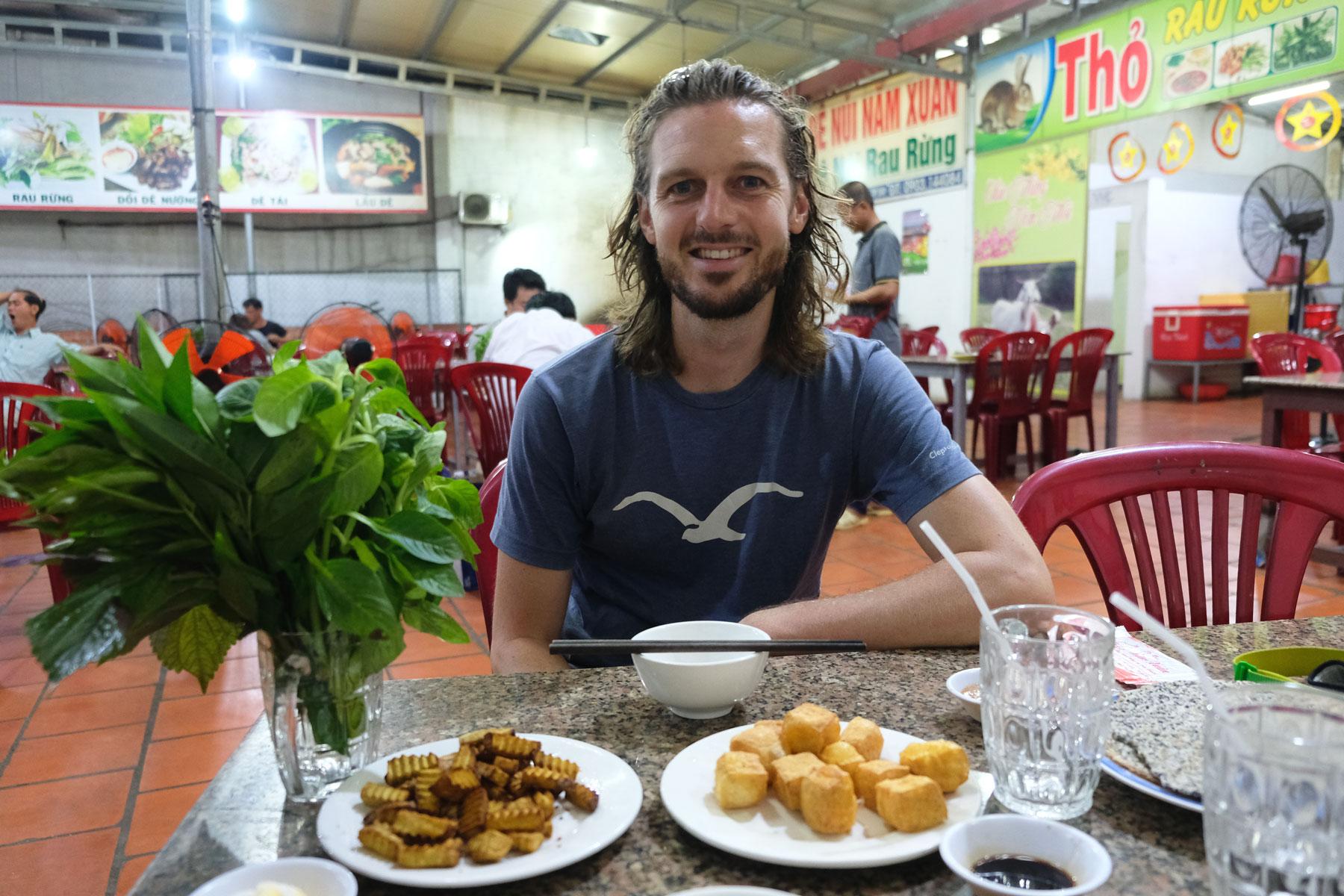 Sebastian sitzt vor zwei Tellern Tofu und Taro, unserem Abendessen.