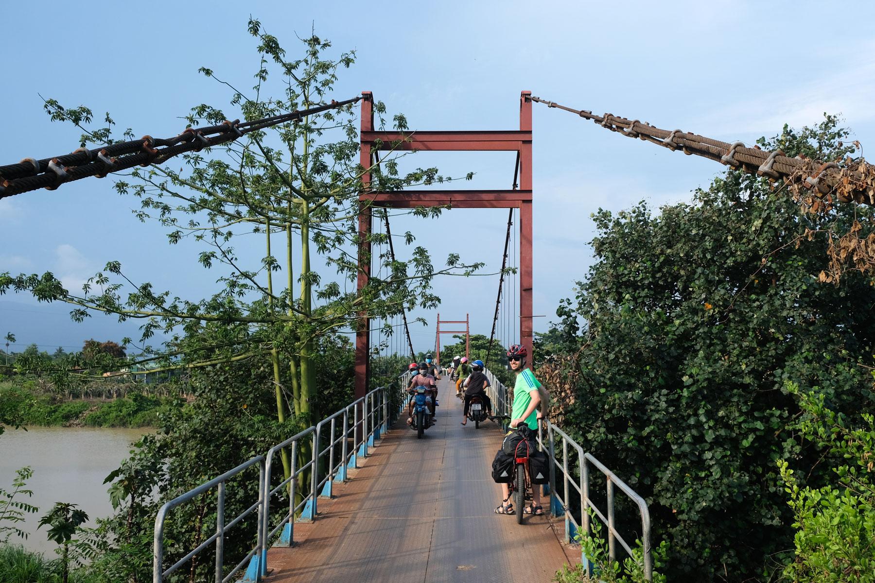 Sebastian steht mit seinem Fahrrad auf einer kleinen Brücke im Süden Vietnams.