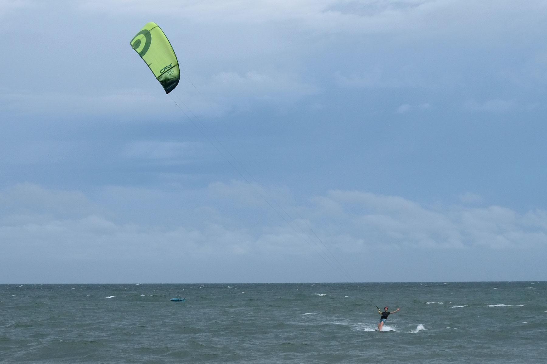 Sebastian fährt auf einem Kiteboard über das Meer vor Mui Ne in Vietnam.